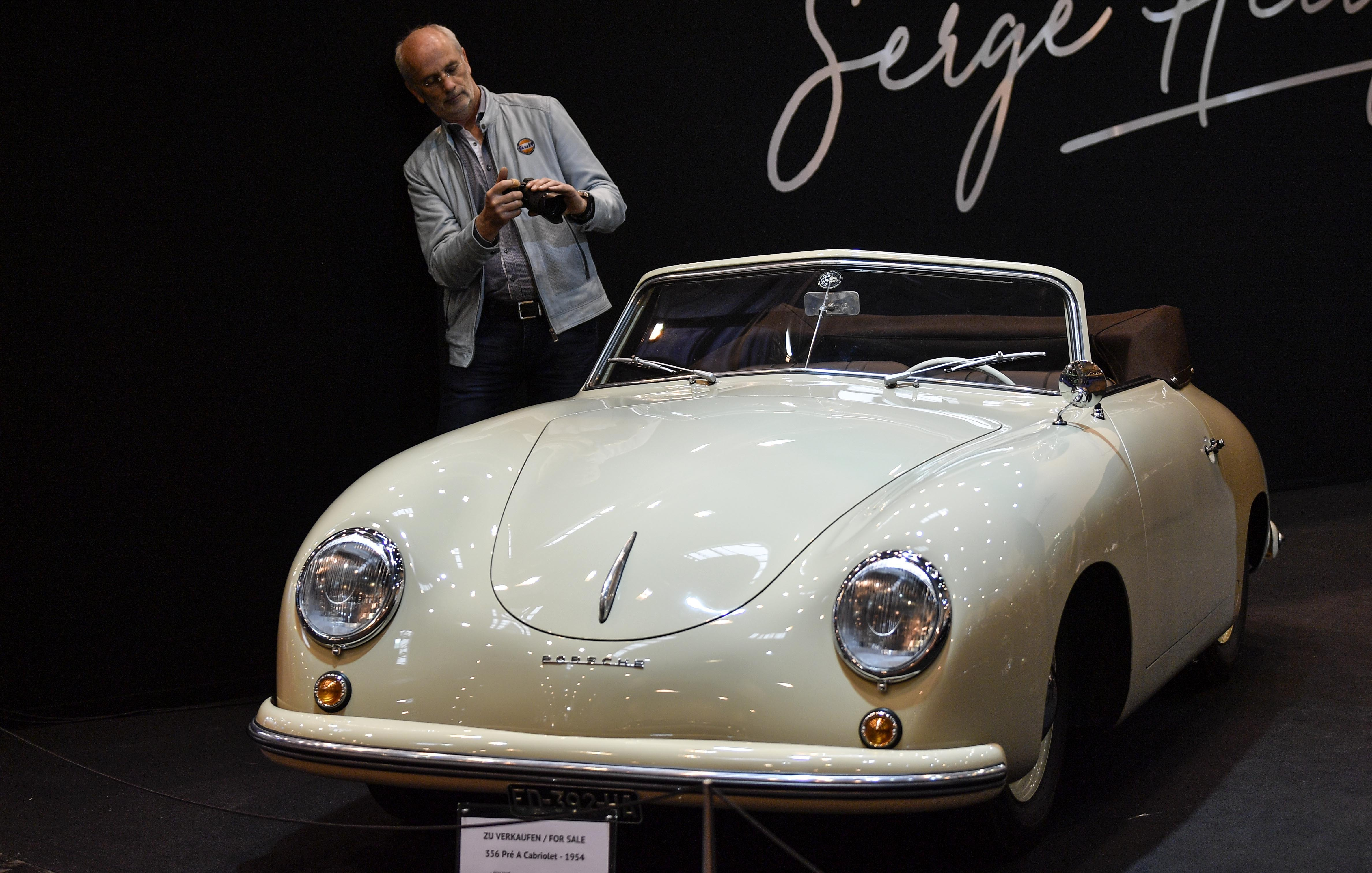 A man takes a picture of a Porsche 356 Cabriolet from 1954 on sale at the World Show for Vintage, Classic and Prestige Automobiles Techno-Classica in Essen, Germany, Friday, April 12, 2019. (AP Photo/Martin Meissner)