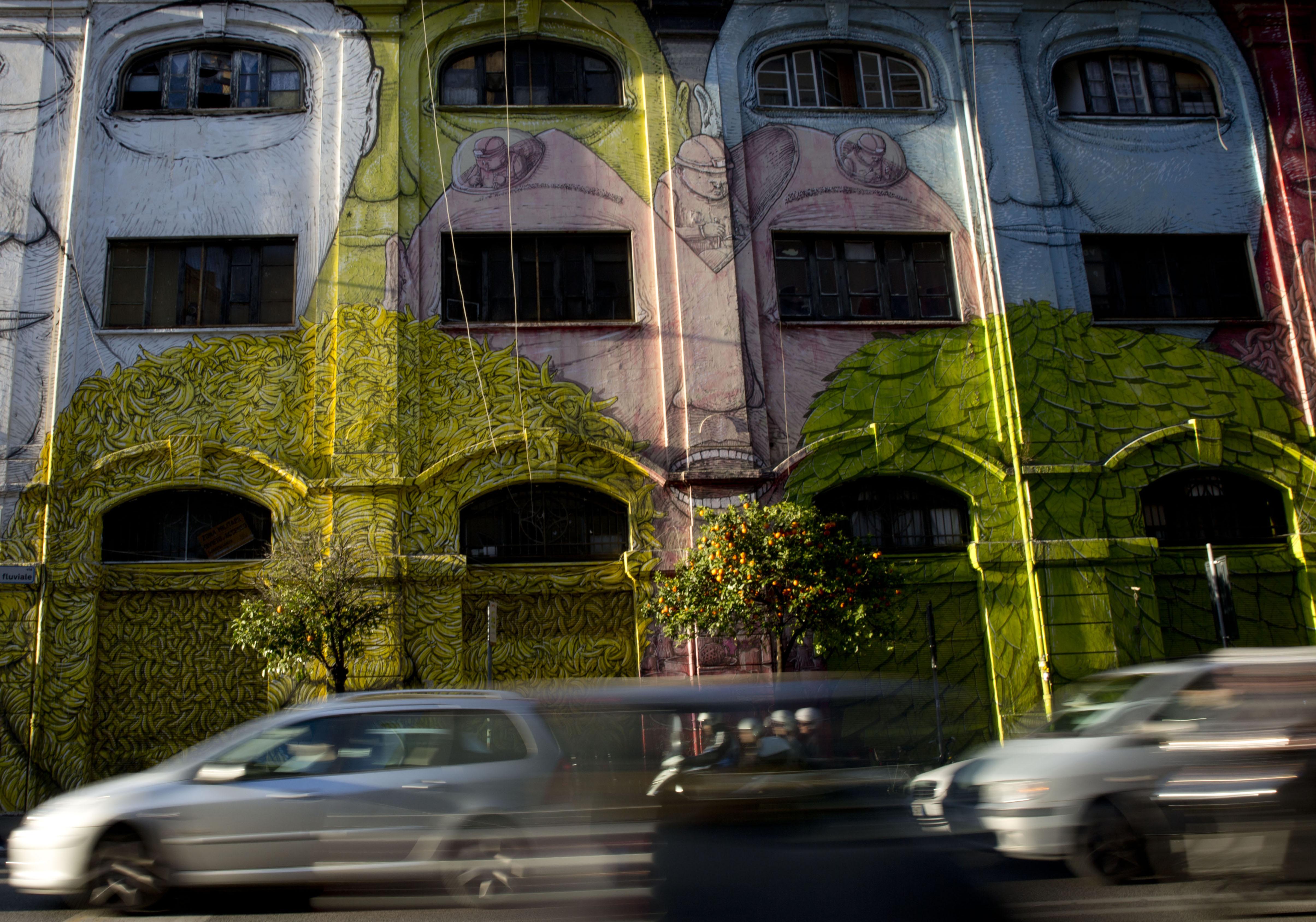 Cars run past a mural painted by Italian artist Blu in Rome, Wednesday, April 1, 2015. (AP Photo/Alessandra Tarantino)