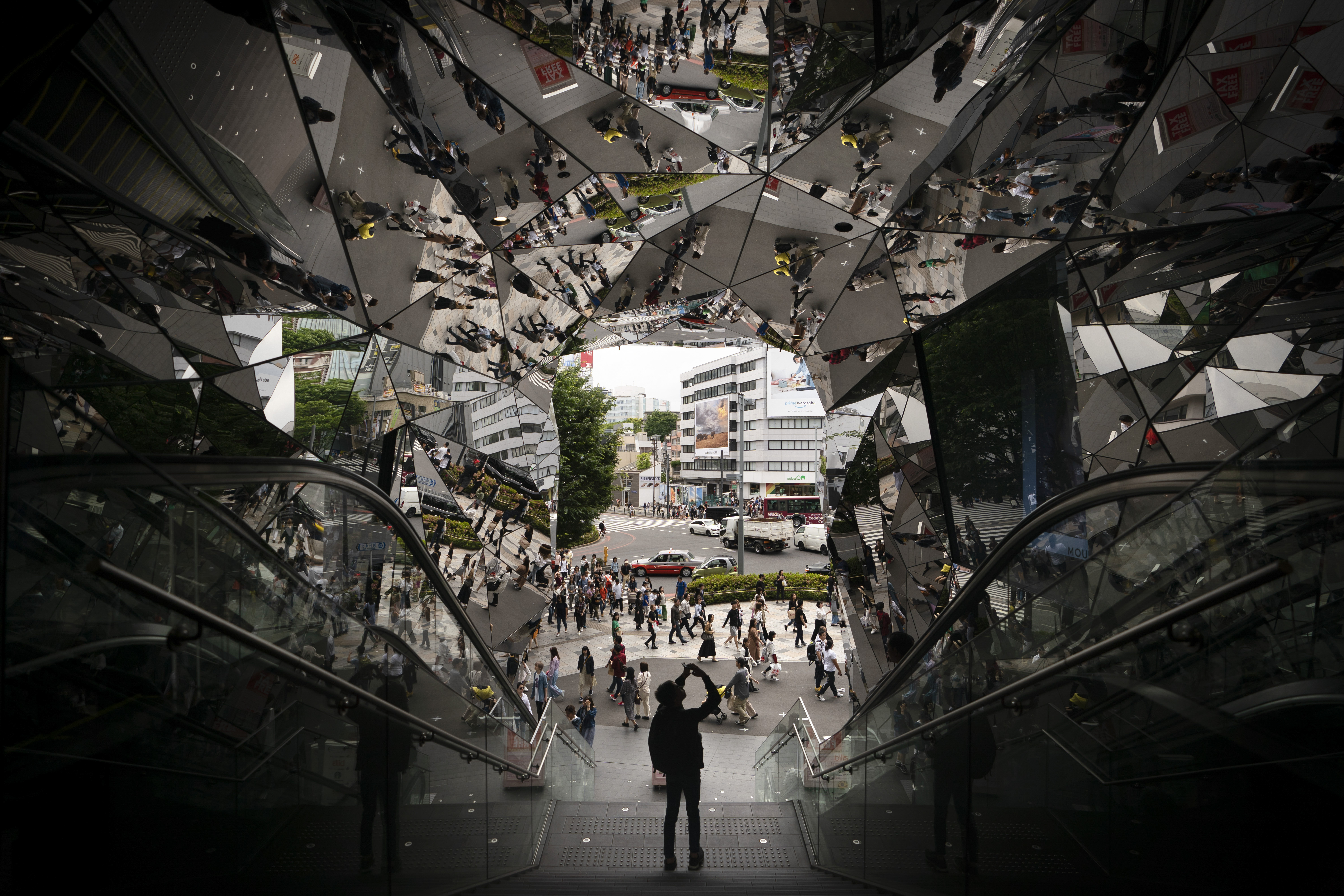 A tourist takes pictures in the entrance way to a shopping mall decorated with mirrors Saturday, May 18, 2019, in Harajuku district of Tokyo. (AP Photo/Jae C. Hong)