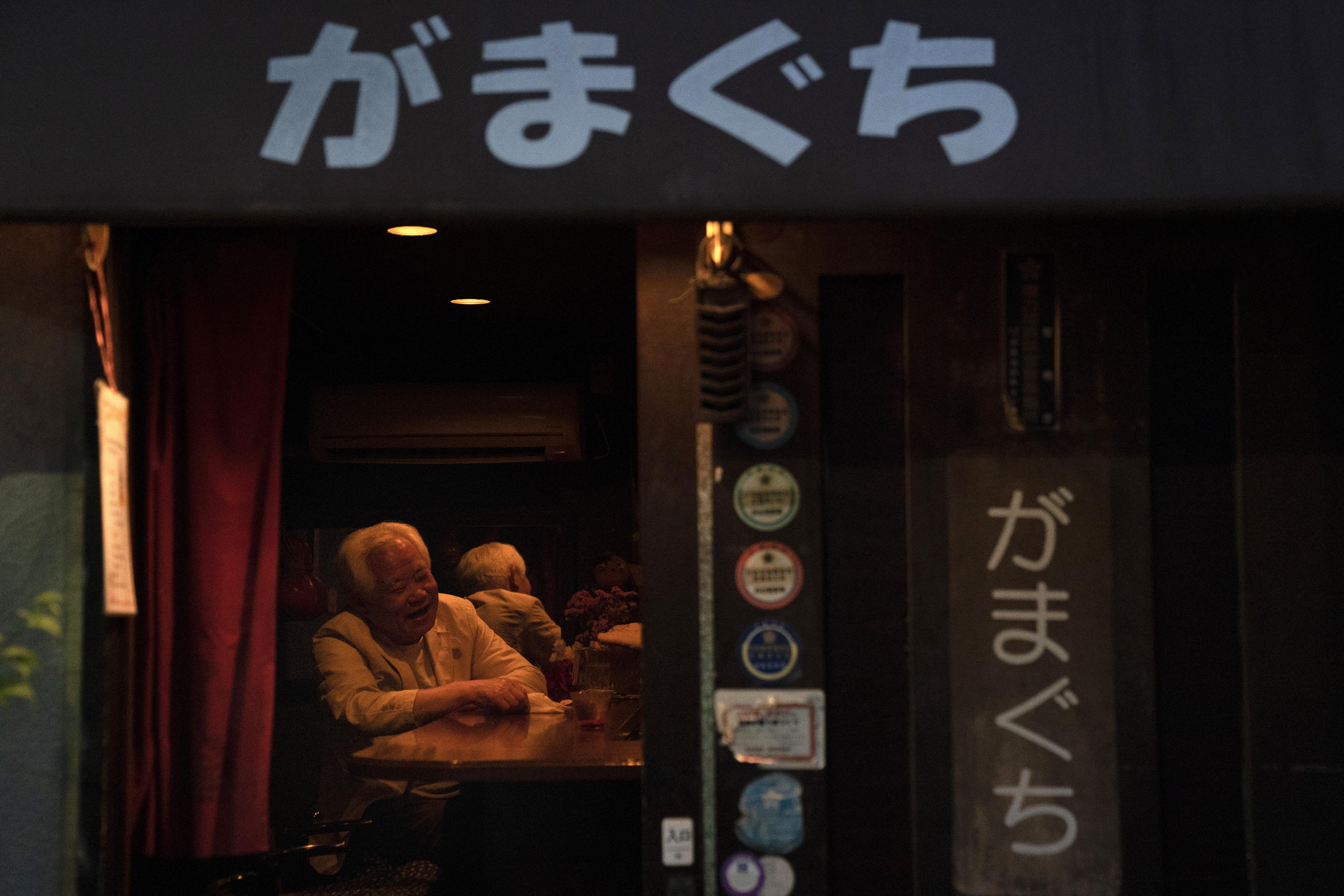 A man shares a laugh with a bartender at a tiny bar Saturday, May 18, 2019, in Shinjuku district in Tokyo. (AP Photo/Jae C. Hong)