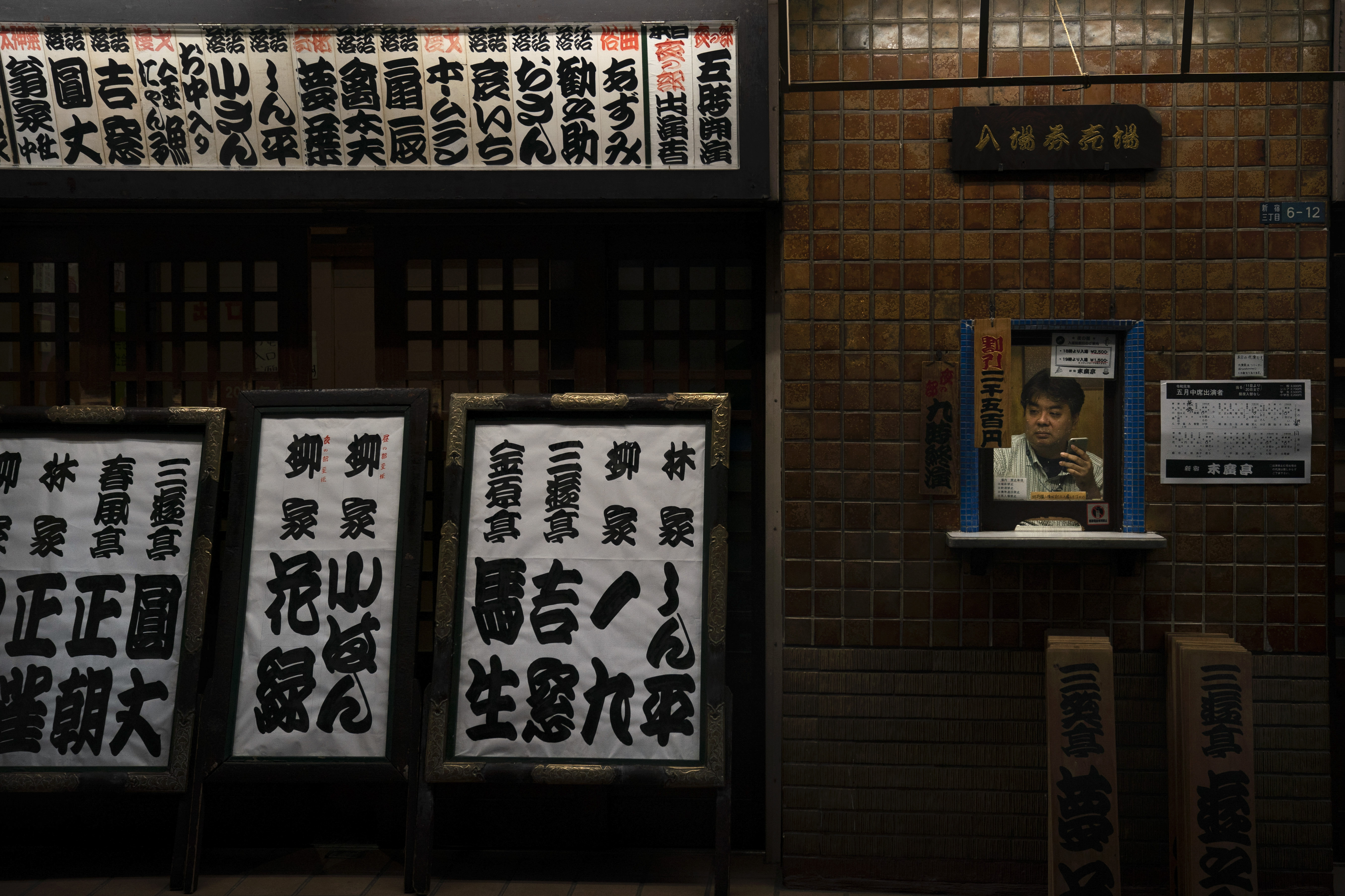 An employee sits in a ticket booth at Suehirotei yose, an entertainment hall where traditional Japanese storytelling called rakugo is performed, Monday, May 20, 2019, in Shinjuku district in Tokyo. (AP Photo/Jae C. Hong)