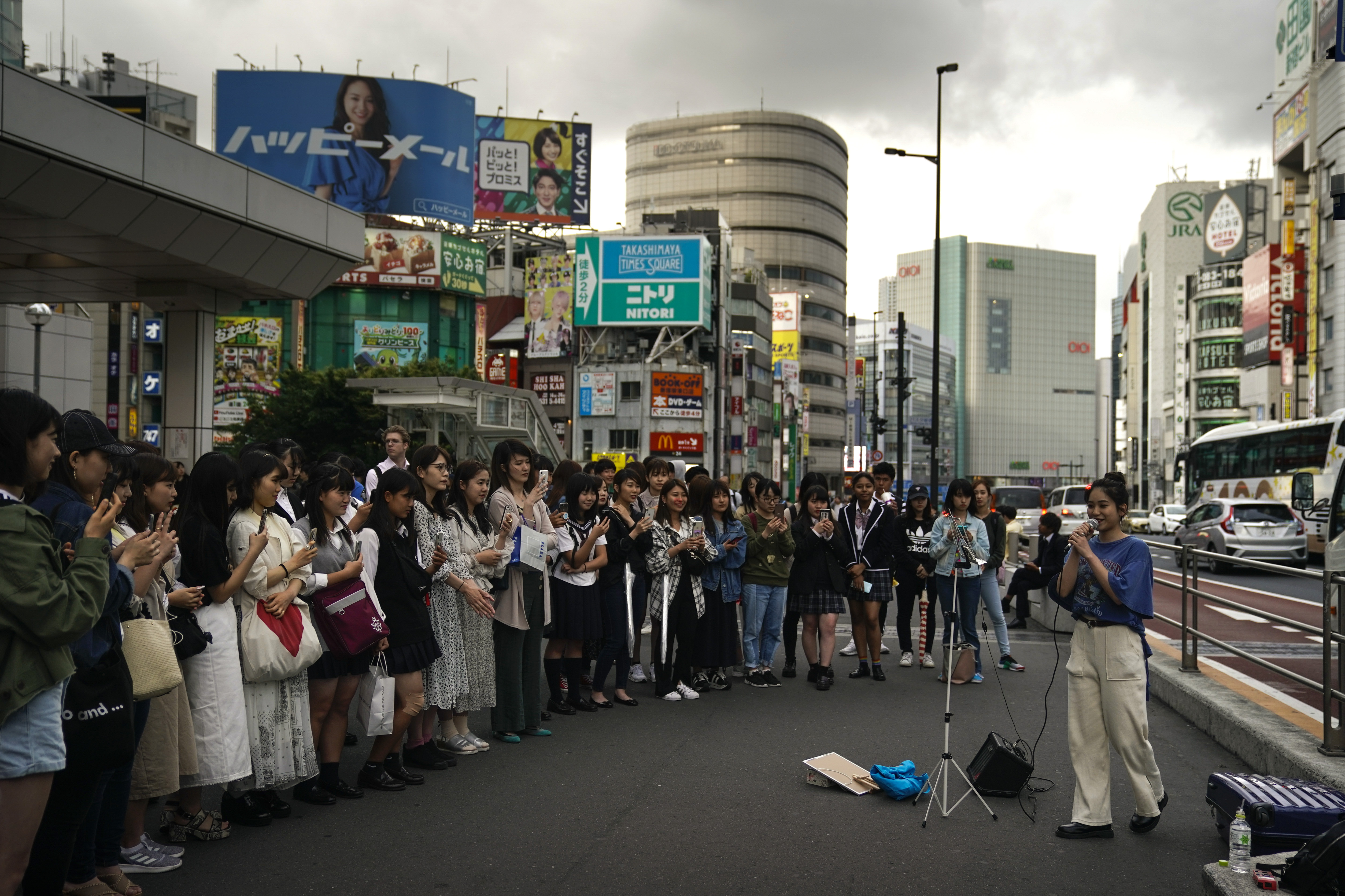 A street performer sings as she is surrounded by spectators outside the Shinjuku Station Monday, May 20, 2019, in Tokyo. (AP Photo/Jae C. Hong)