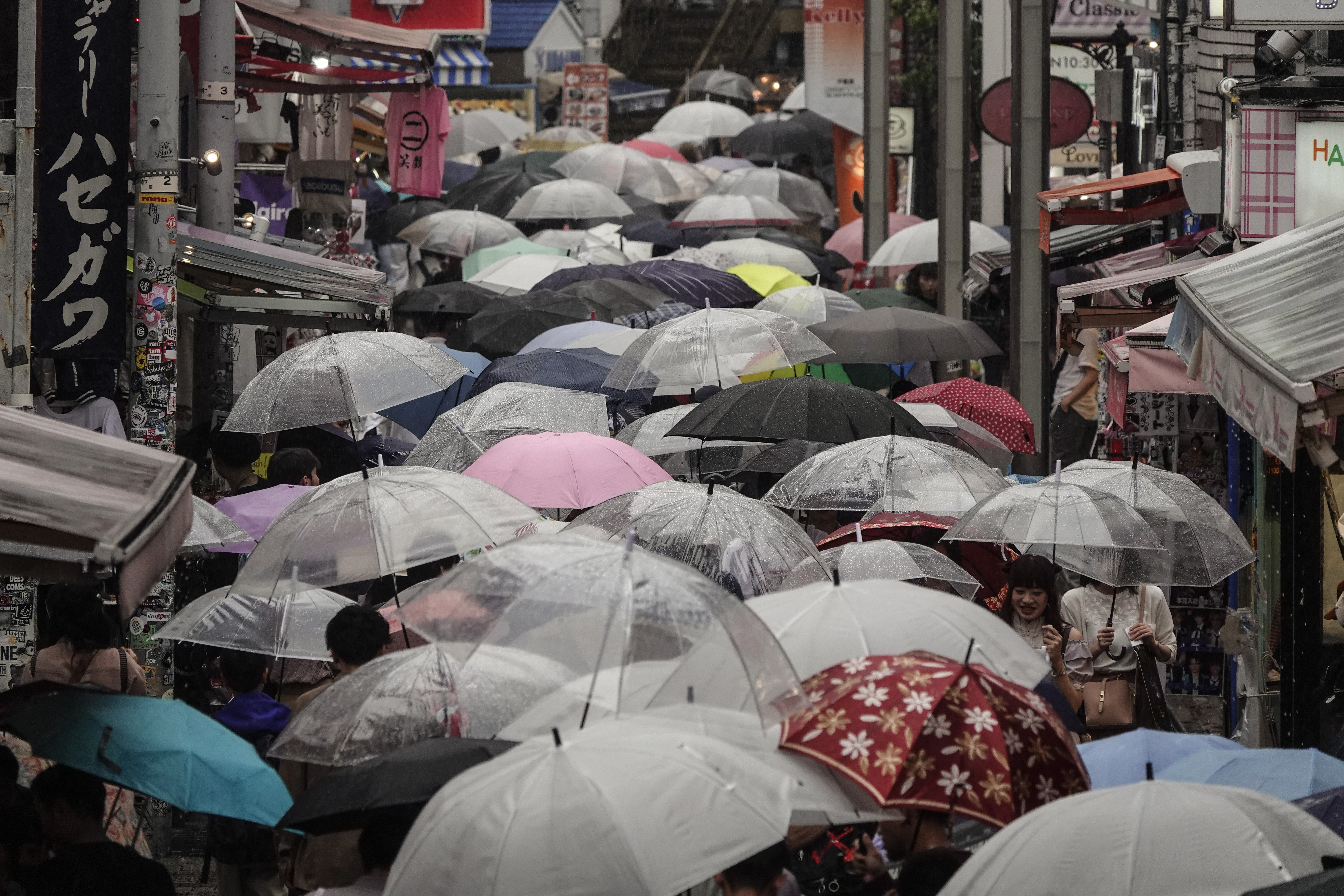 Shoppers with umbrellas walk along the Takeshita Street Friday, June 7, 2019, in the Harajuku district of Tokyo. Harajuku is one of the most popular shopping neighborhoods in Tokyo. (AP Photo/Jae C. Hong)