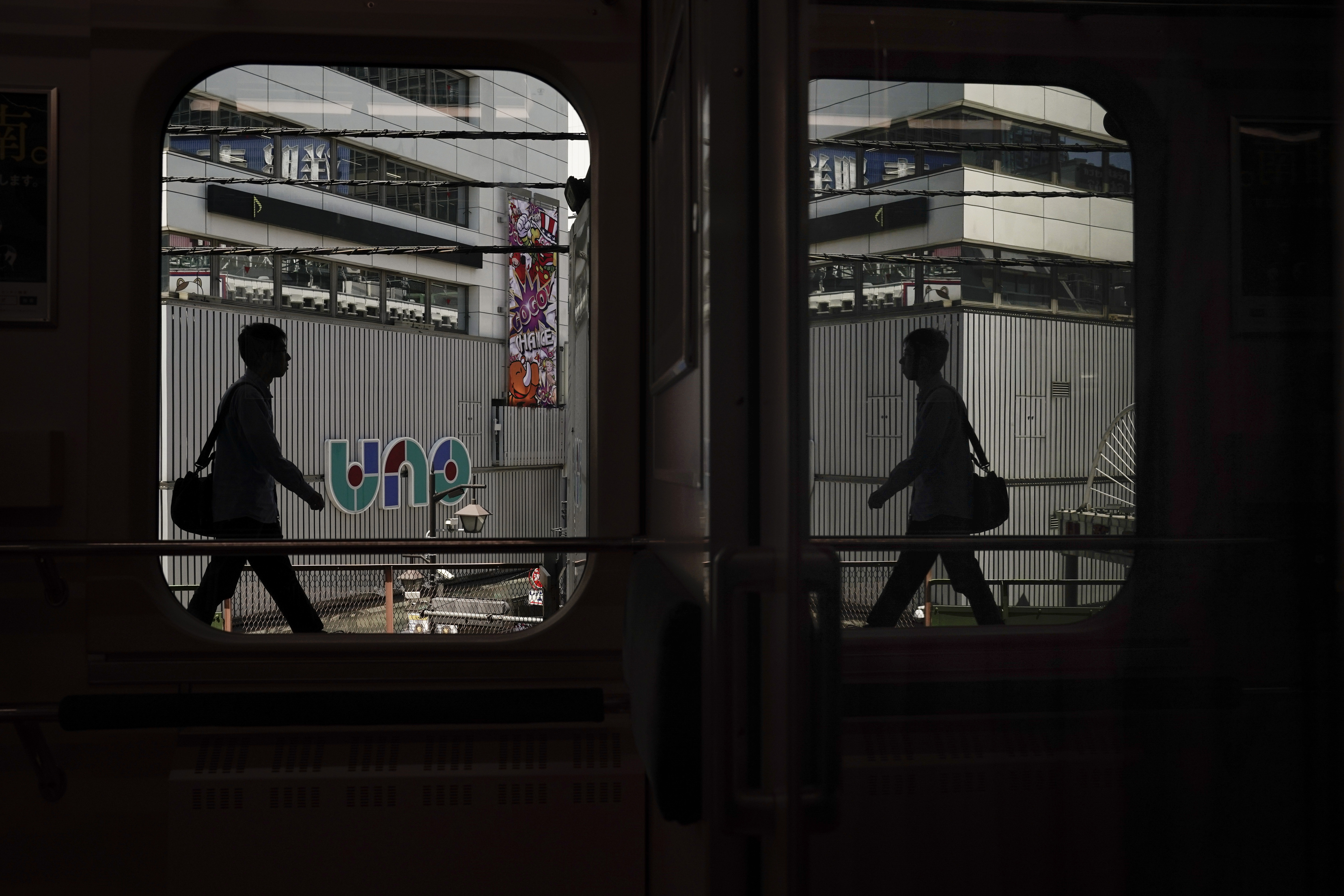 In this May 22, 2019, photo, a commuter is reflected in the window of a Yamanote Line train as he gets off at Shimbashi Station in Tokyo. Running above ground, views from wide windows on the train range from high-rises to local shopping arcade as the train covers different parts of the city. The line, according to company statistics, moves roughly 3 to 4 million people daily, more than the entire population of Jamaica. (AP Photo/Jae C. Hong)
