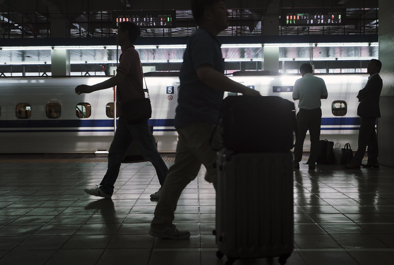 Passengers walk at platform for bullet trains or Shinkansen Monday, June 10, 2019, at Hakata Station in Fukuoka, western Japan. (AP Photo/Eugene Hoshiko)