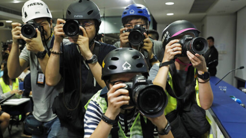 Press photographers wearing helmets for protection in the clashes seen in recent protests, photograph a press conference by Commissioner of Police Stephen Lo in Hong Kong, Thursday, June 13, 2019. (AP Photo/Vincent Yu)