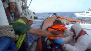 Lo sbarco di un bambino, tra le 10 persone autorizzate a lasciare la Sea Watch per Lampedusa, in un'immagine postata dalla stessa Ong sul suo profilo Twitter, 16 giugno 2019.