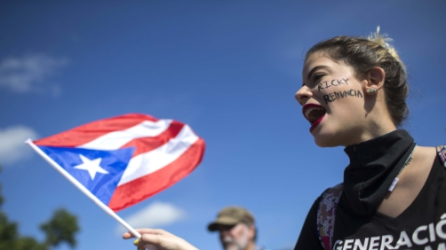 A woman flies a Puerto Rico flag during a protest to demand the resignation of Governor Ricardo Rossello from office, in San Juan, Puerto Rico, Monday, July 22, 2019. Protesters are demanding Rossello step down for his involvement in a private chat in which he used profanities to describe an ex-New York City councilwoman and a federal control board overseeing the island's finance. (AP Photo/Dennis M. Rivera Pichardo)
