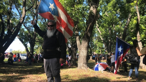 German Alejandro Ortiz, a 43-year-old businessman holds a Puerto Rico flag as he poses for a photo during a protest to demand the resignation of Governor Ricardo Rossello, in San Juan, Puerto Rico, Monday, July 22, 2019. Ortiz explained why he decided to join the protest: