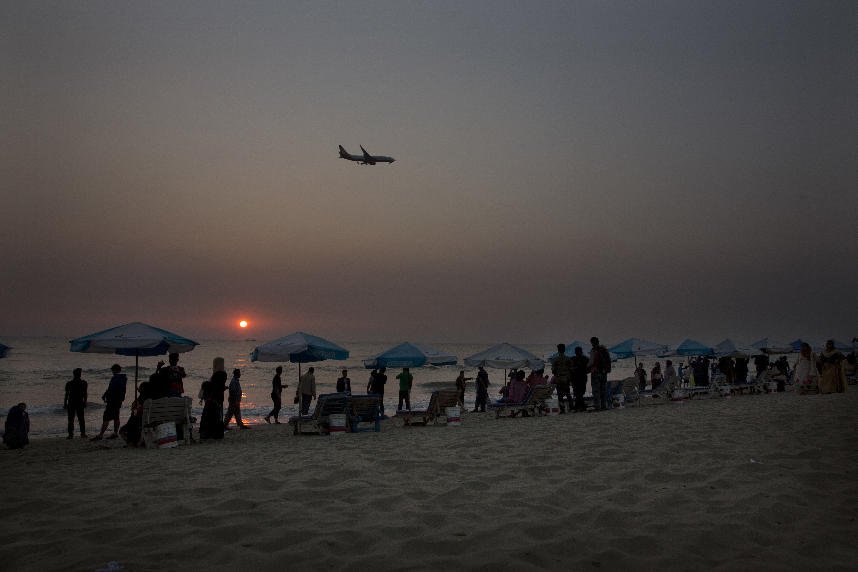 Bangladeshis enjoy sunset at a beach as an aeroplanes flies past in Cox's Bazar, Bangladesh Friday, Jan. 26, 2018. Miles-long beaches makes this coastal district Bangladesh's top tourist destination. (AP Photo/Manish Swarup)