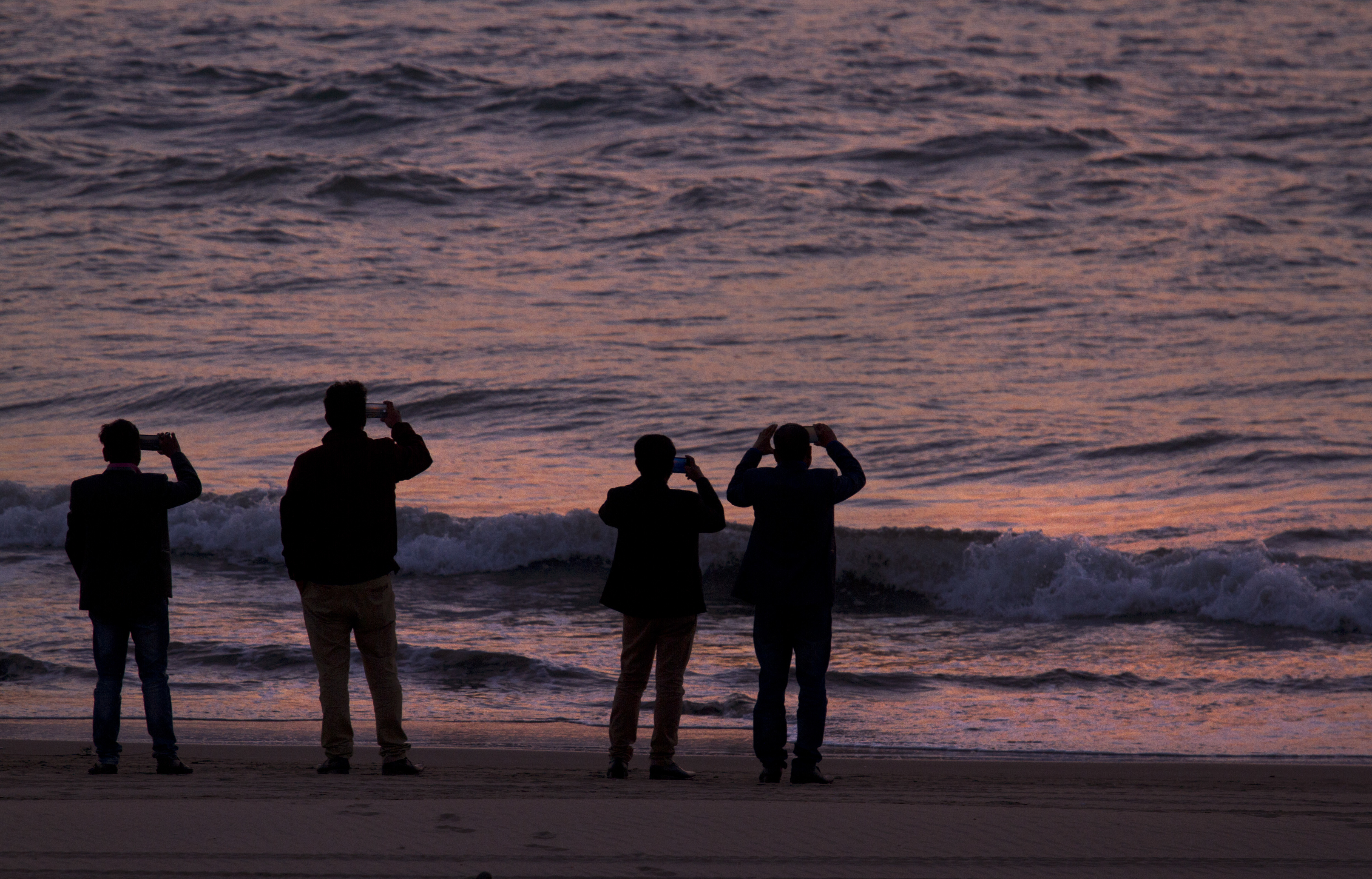 Local tourists record the setting Sun on the Bay of Bengal from the beach in Cox's Bazar, Bangladesh, Sunday, Jan. 28, 2018. Miles-long beaches makes this coastal district Bangladesh's top tourist destination. (AP Photo/Manish Swarup)