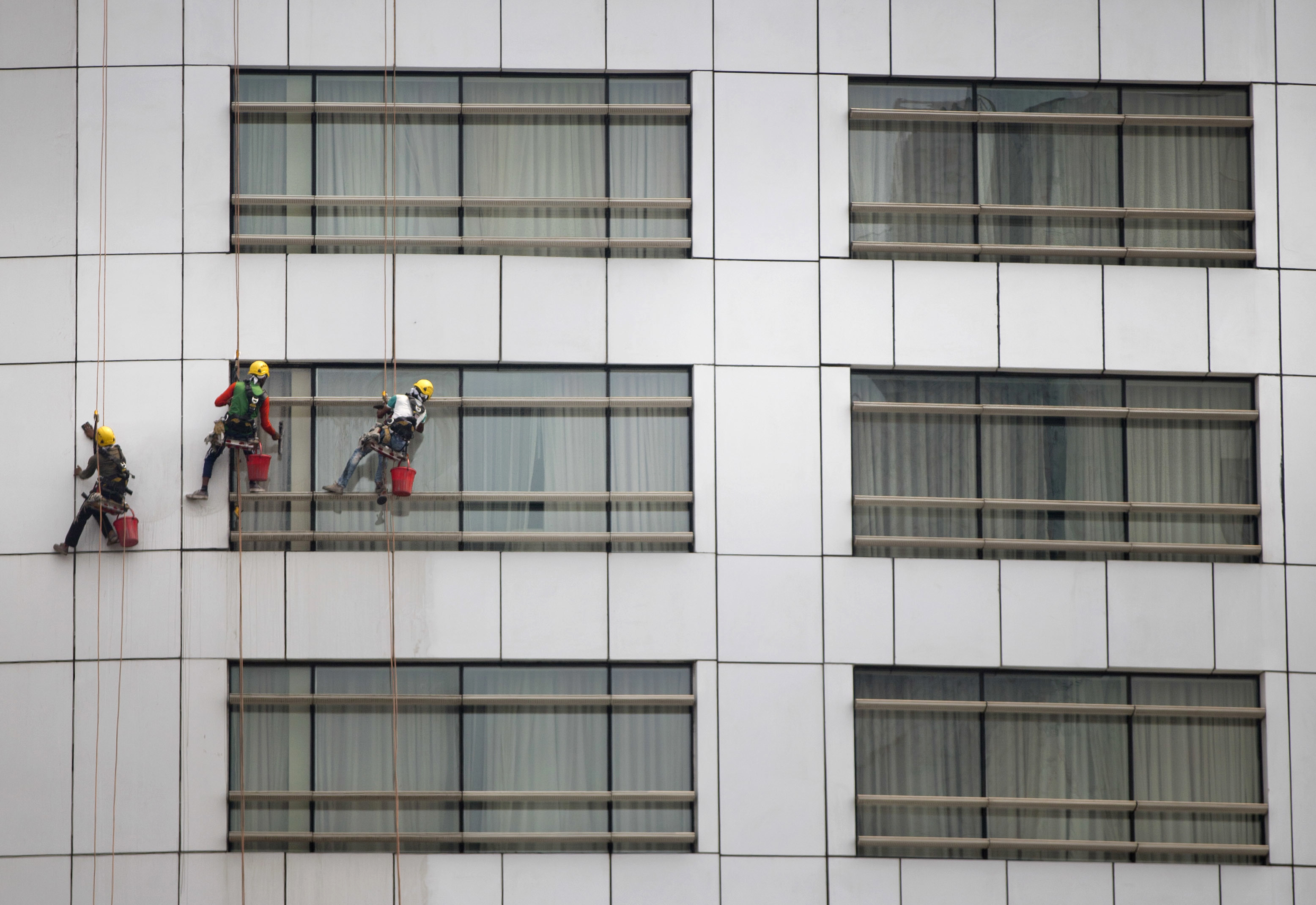 Window cleaners work on glass panes of an office building in Dhaka, Bangladesh, Saturday, March 24, 2018. On an average, each worker earns less than US$5 a day. (AP Photo/A.M. Ahad)