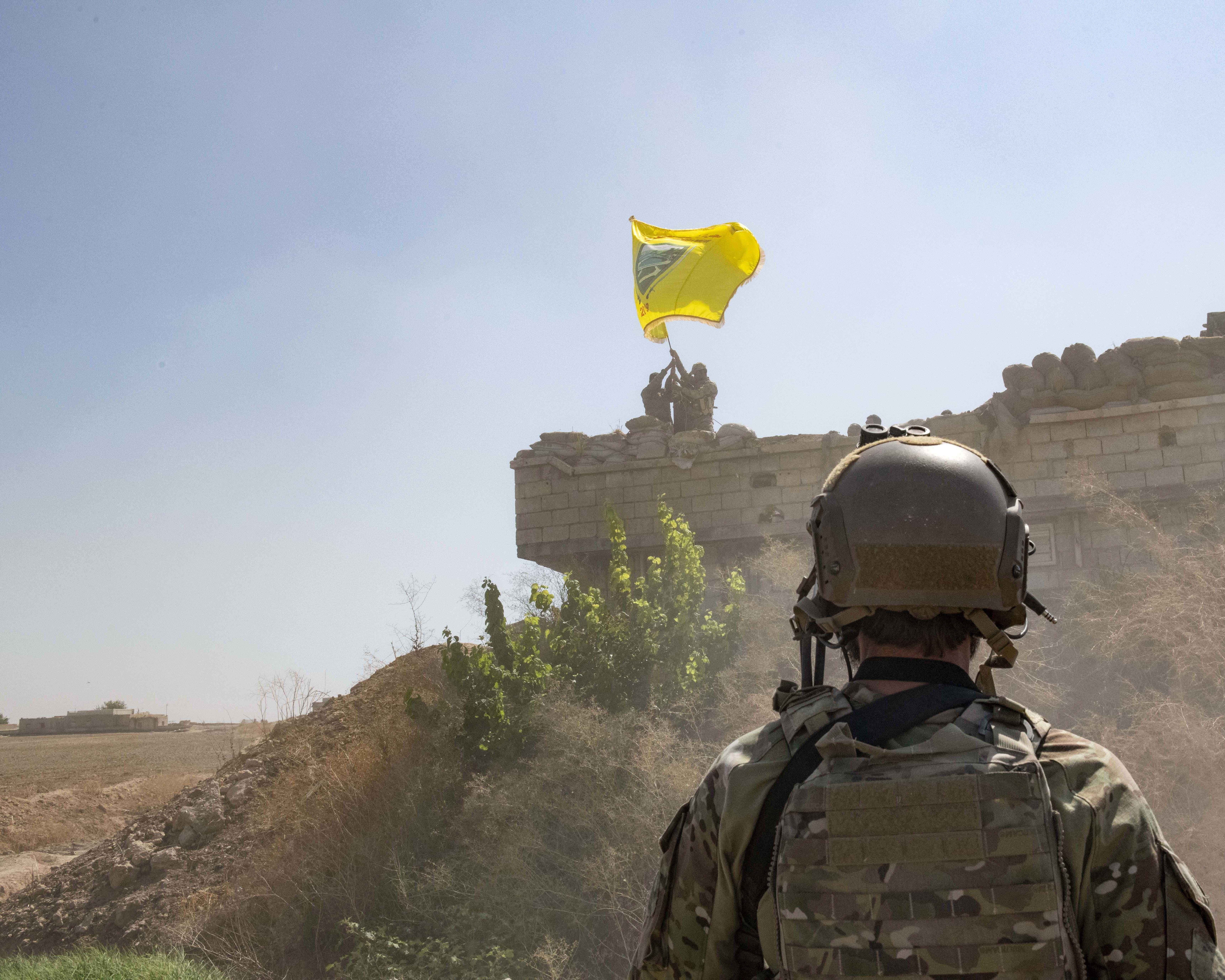 In this Sept. 21, 2019, photo, released by the U.S. Army, a U.S. soldier oversees members of the Syrian Democratic Forces as they demolish a Kurdish fighters' fortification and raise a Tal Abyad Military Council flag over the outpost as part of the so-called