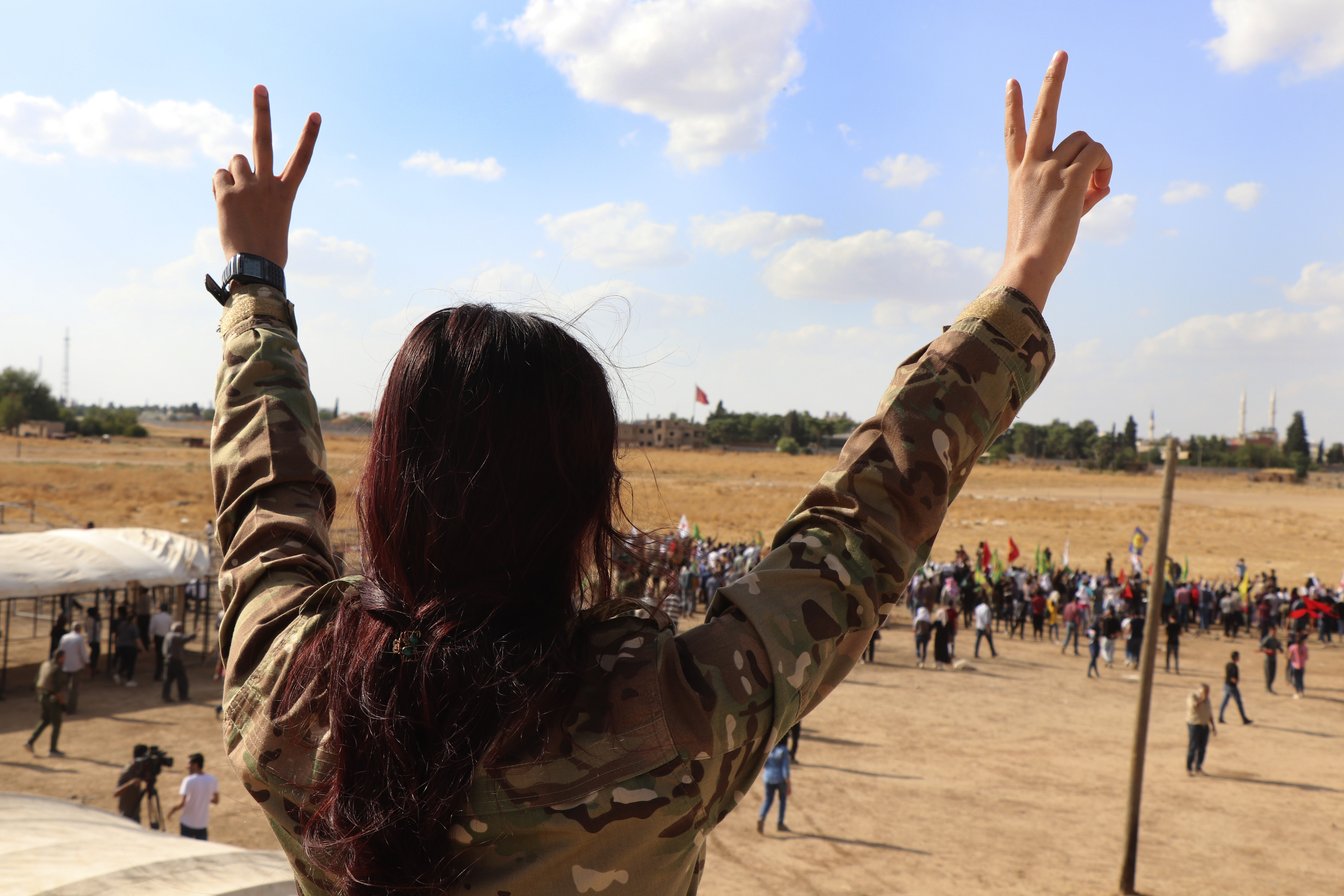 A fighter from the Syrian Democratic Forces, SDF, flashes the victory sign during a demonstration against possible Turkish military operation on their areas, at the Syrian-Turkish border, in Ras al-Ayn, Syria, Monday, Oct. 7, 2019. Syria's Kurds accused the U.S. of turning its back on its allies and risking gains made in the fight against the Islamic State group as American troops began pulling back on Monday from positions in northeastern Syria ahead of an expected Turkish assault. (AP Photo)