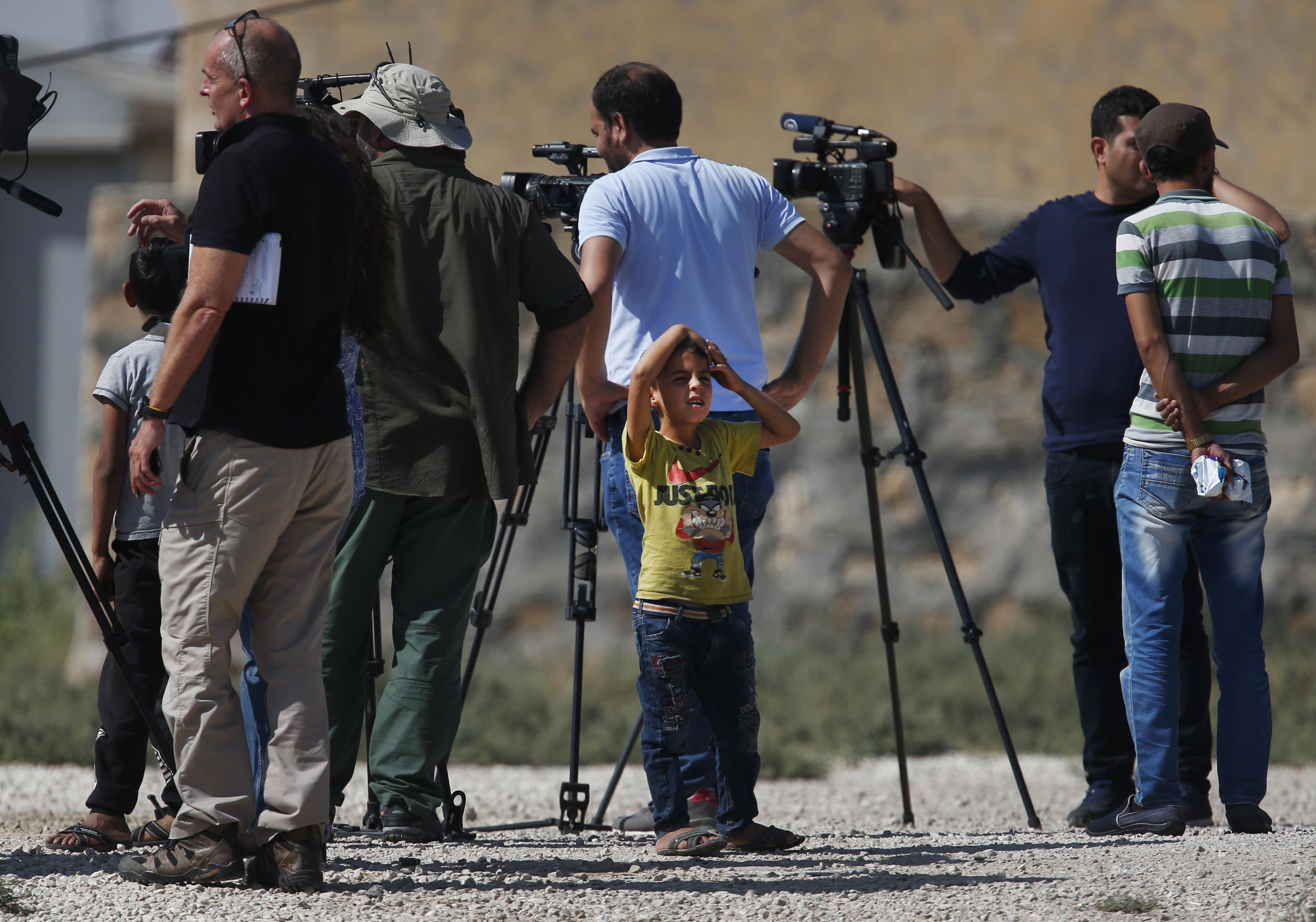 Residents look on as members of the media work at the border between Turkey and Syria, in Akcakale, Sanliurfa province, southeastern Turkey, Tuesday, Oct. 8, 2019. Turkey's vice president Fuat Oktay says his country won't bow to threats in an apparent response to U.S. President Donald Trump's warning to Ankara about the scope of its planned military incursion into Syria. (AP Photo/Lefteris Pitarakis)
