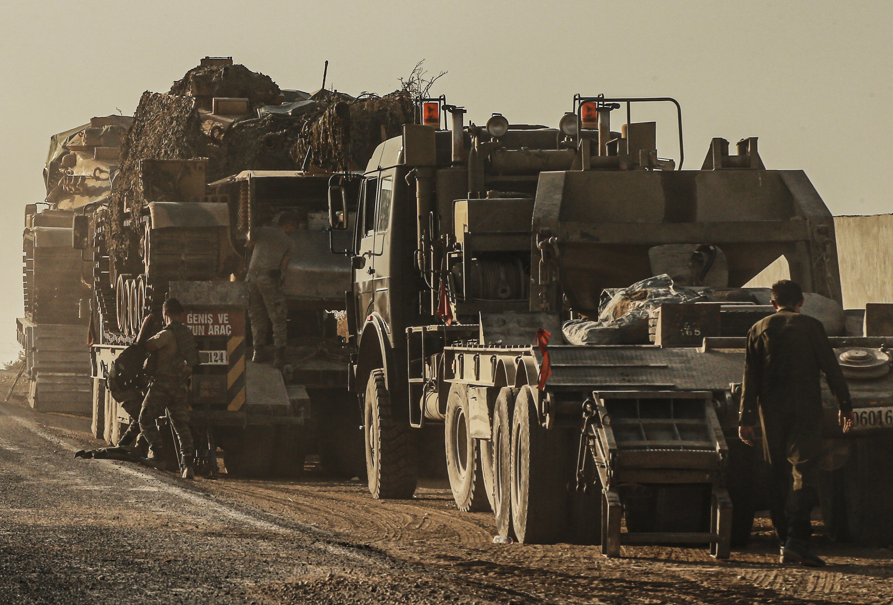 Turkish soldiers work on uploading tanks from trucks on a road towards the border of Syria in Sanliurfa province, Turkey, Monday, Oct. 14, 2019. Syrian troops entered several northern towns and villages Monday, getting close to the Turkish border as Turkey's army and opposition forces backed by Ankara marched south in the same direction, raising concerns of a clash between the two sides as Turkey's invasion of northern Syria entered its sixth day. (AP Photo/Emrah Gurel)