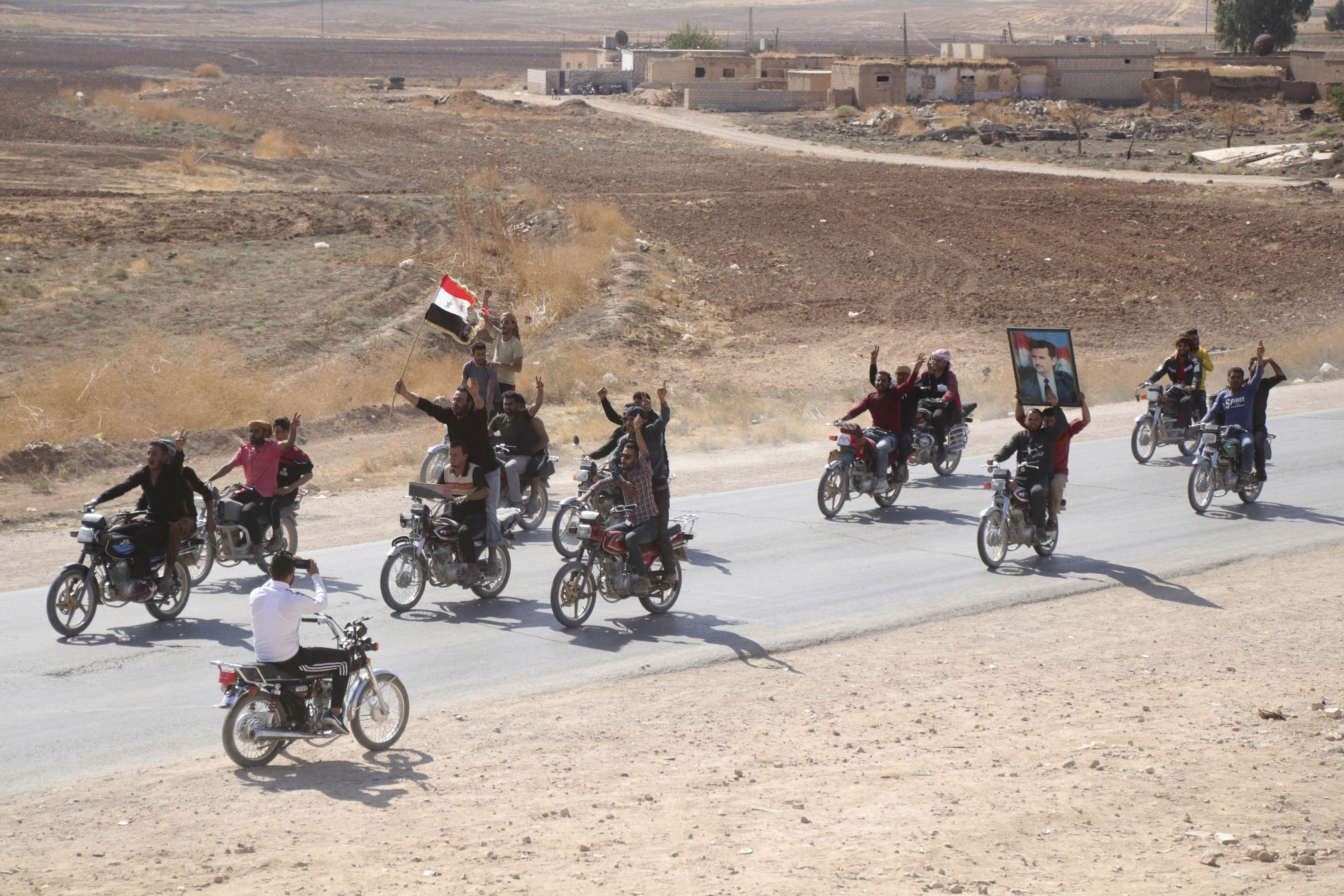 People ride motorcycles and hold a Syrian flag and a portrait of Syrian President Bashar Assad as they welcome Syrian troops as they enter the village of Ghebesh, west of the town of Tal Tamr, in northern Syria, Monday, Oct 14, 2019. Syrian government troops moved into towns and villages in northern Syria on Monday, setting up a potential clash with Turkish-led forces advancing in the area as long-standing alliances in the region begin to crumble following the pullback of U.S. forces. (AP Photo)