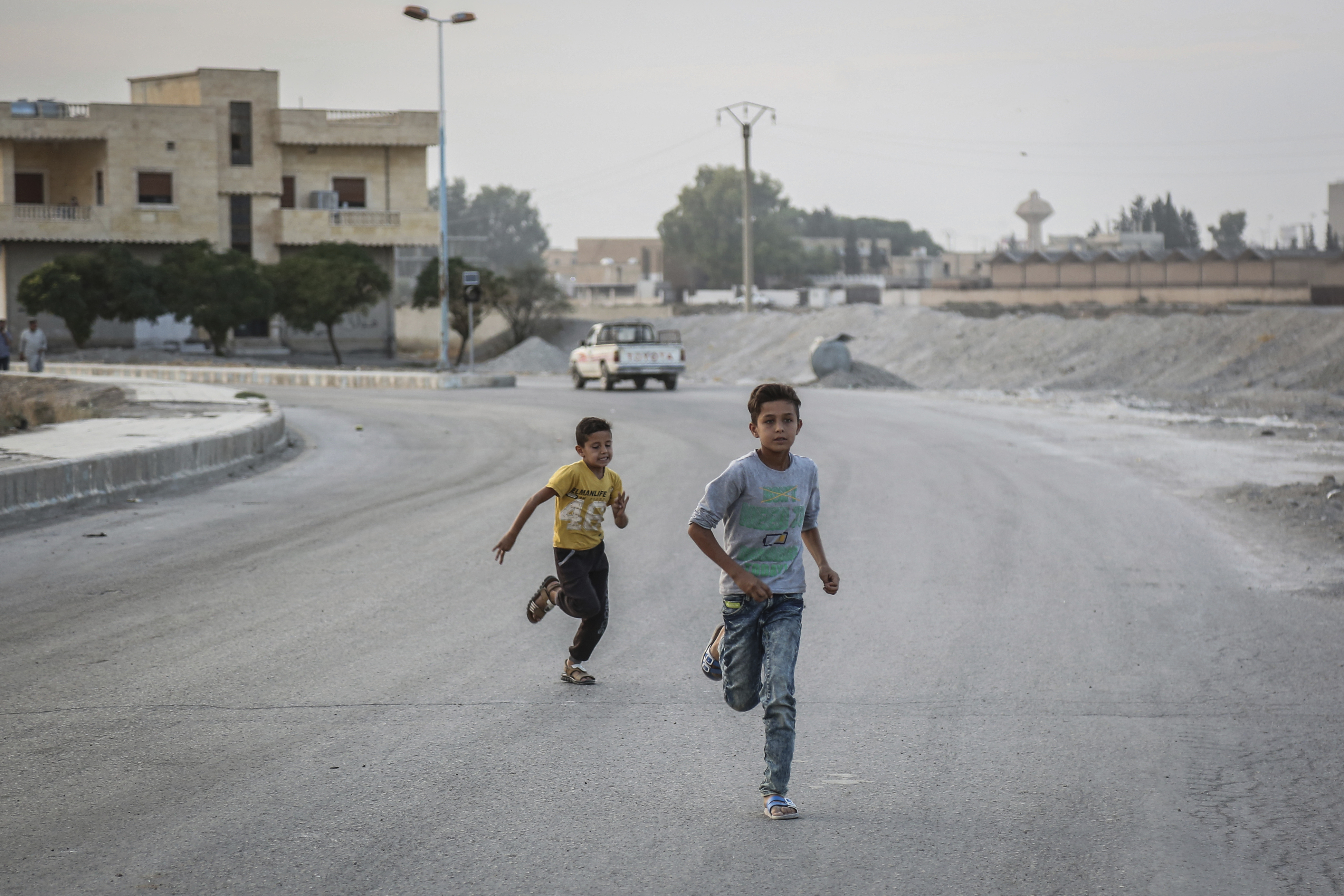 14 October 2019, Syria, Tell Abiad: Two young boys run on a deserted street. Photo by: Anas Alkharboutli/picture-alliance/dpa/AP Images