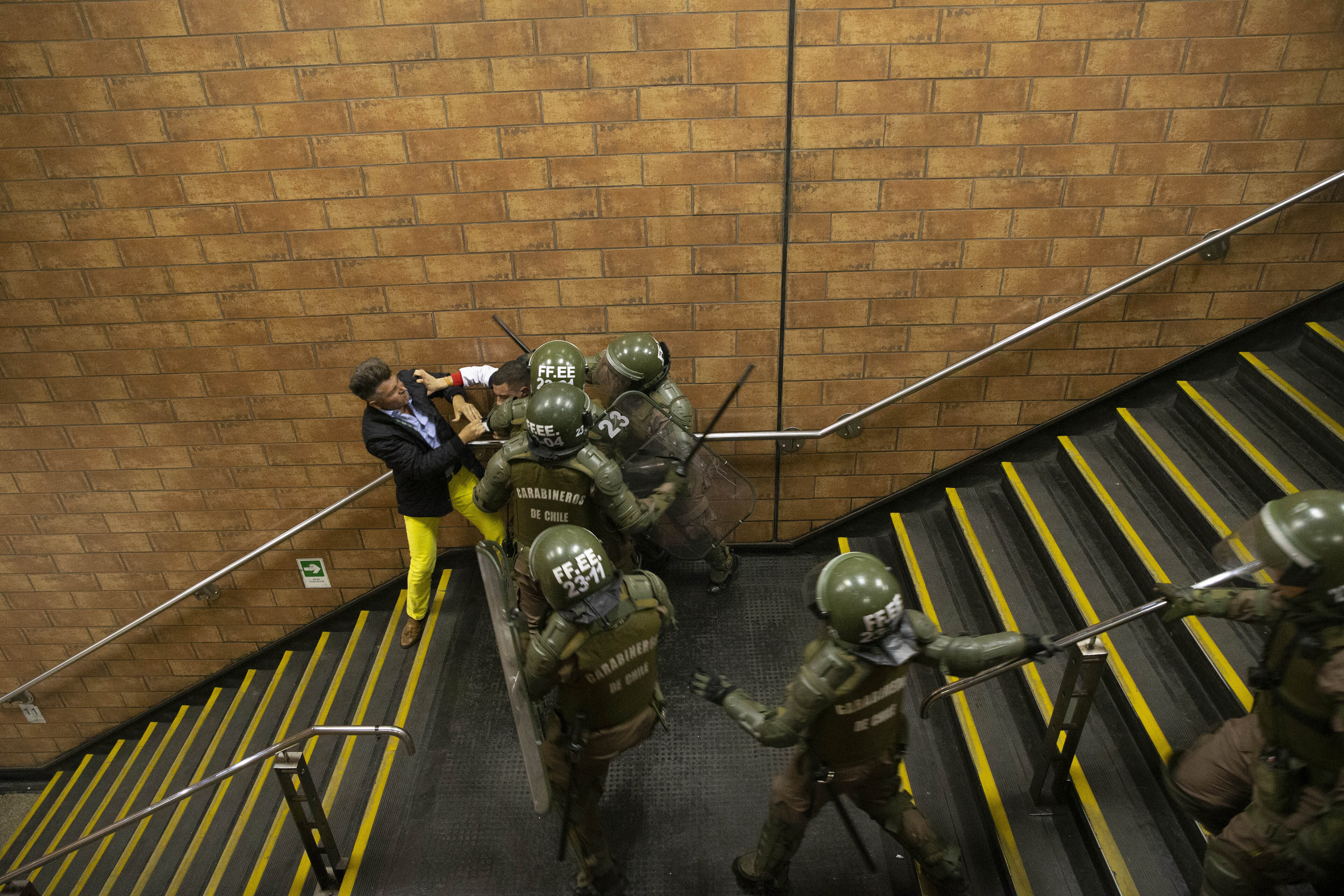 Chilean Carabineros separate two men who were fighting during a student protest against the rising cost of subway and bus fare, in Santiago, Friday, Oct. 18, 2019. (AP Photo/Esteban Felix)