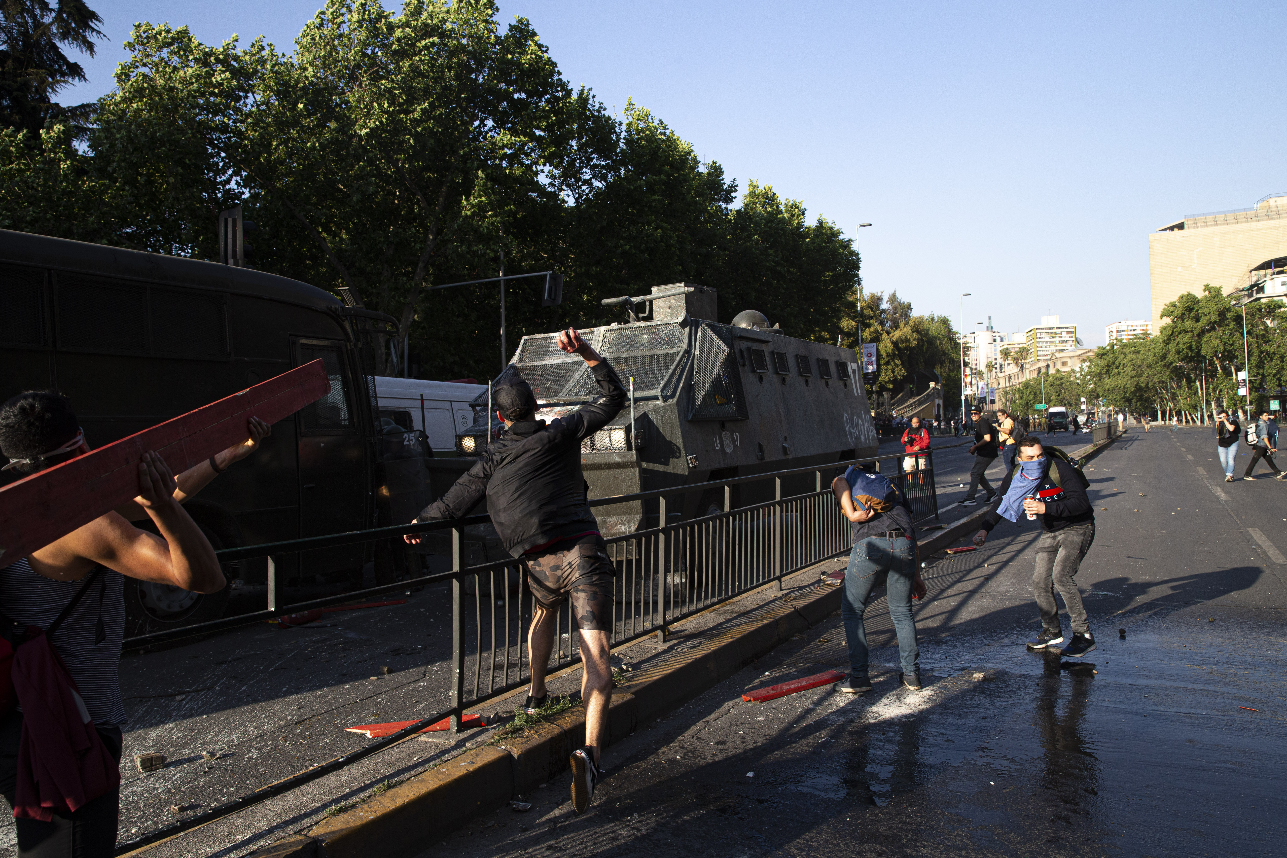 A protester throws a rock at a water cannon during clashes with police in front of the Santa Lucia subway station during a protest against the rising cost of subway and bus fares, in Santiago, Friday, Oct. 18, 2019. (AP Photo/Esteban Felix)