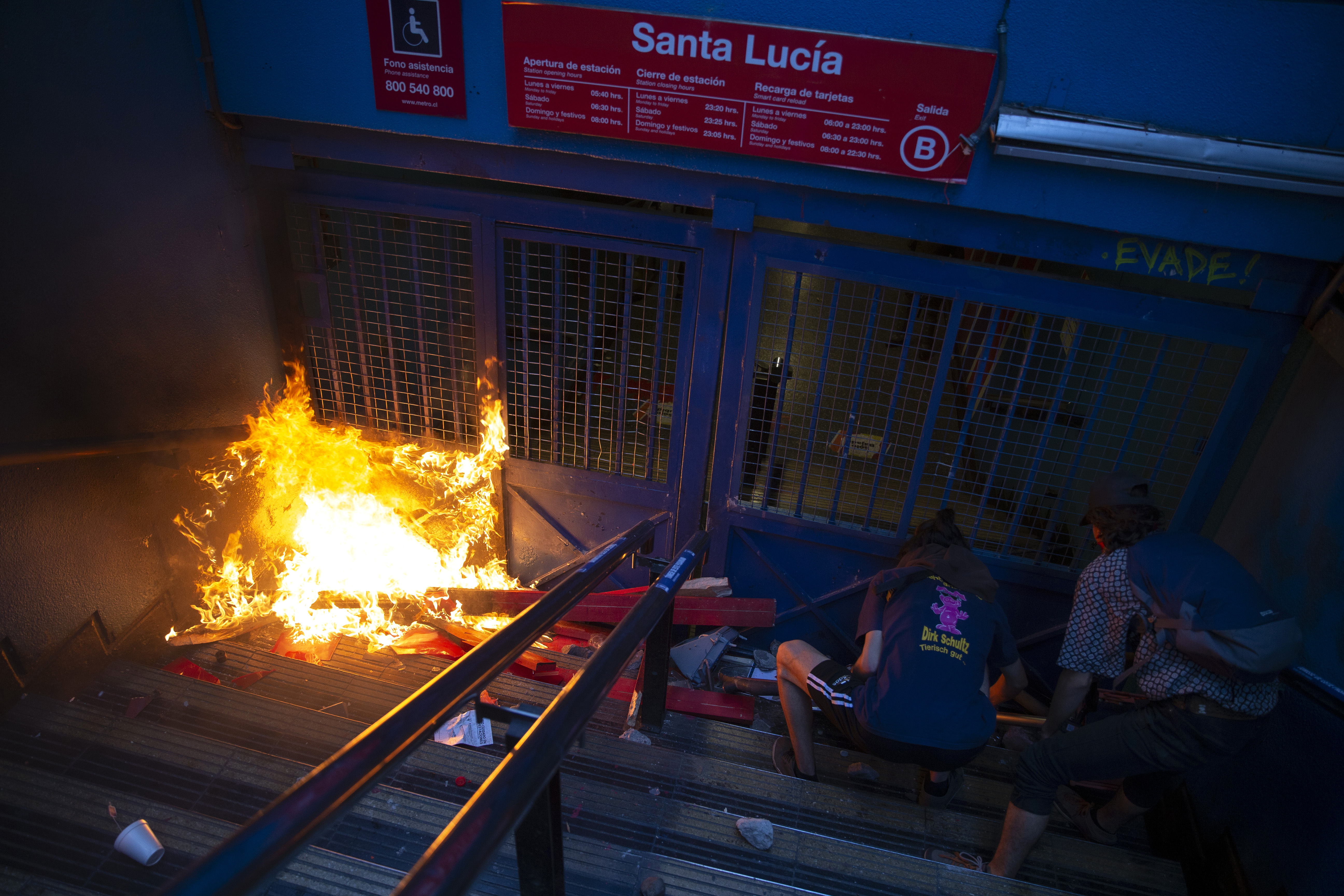 Protesters push a bicycle in front of a gate of the Santa Lucia subway station during a protest against the rising cost of subway and bus fares, in Santiago, Friday, Oct. 18, 2019. (AP Photo/Esteban Felix)