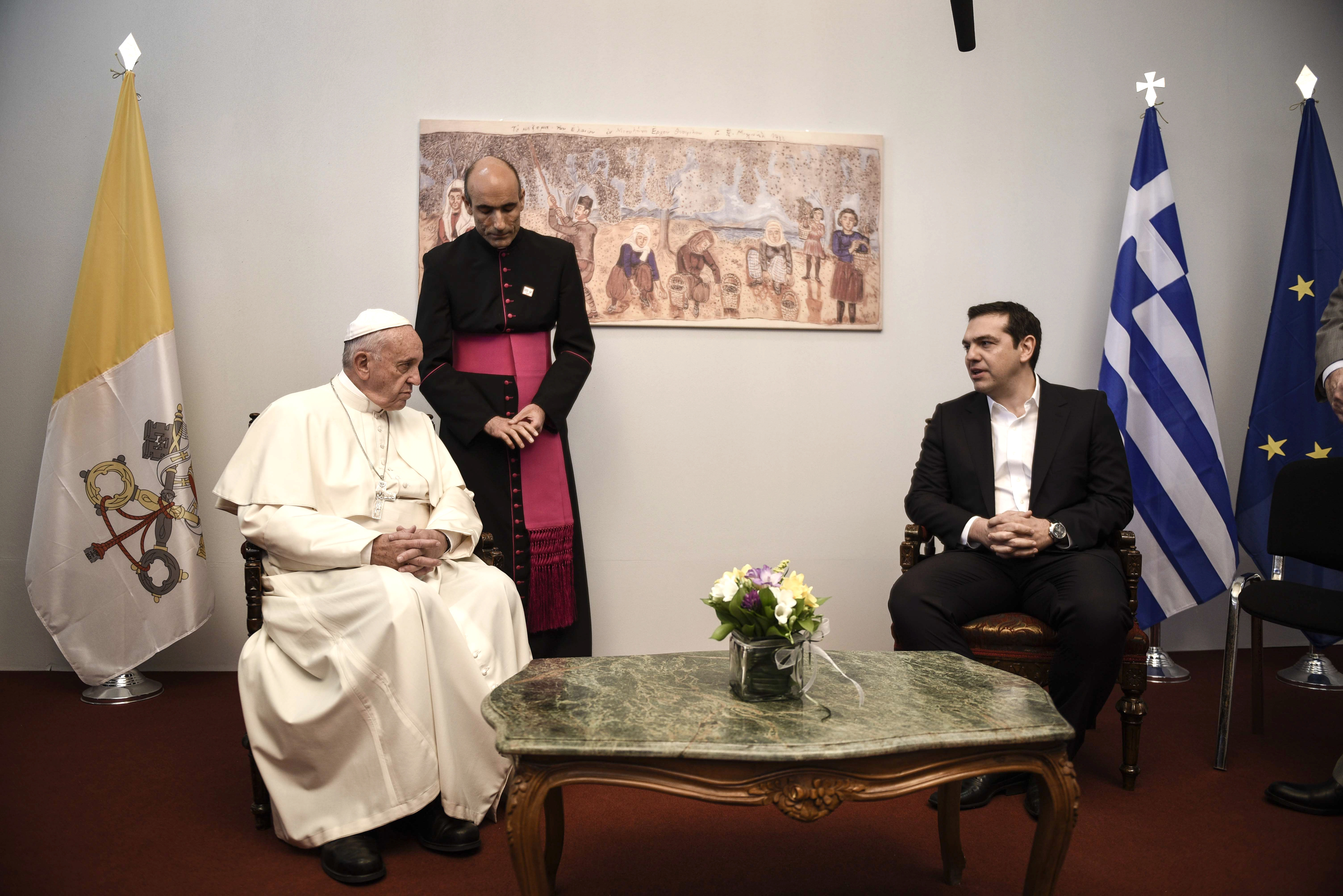 In this photo released by Greek Prime Minister's office on Saturday, Apr. 16, 2016, Greece's Prime Minister Alexis Tsipras, right, meets visiting Pope Francis after his arrival on the island of Lesbos. Pope Francis traveled to Greece on Saturday for a brief but provocative visit to meet with refugees at a detention center as the European Union implements a controversial plan to deport them back to Turkey. (Andrea Bonetti/Greek Prime Minister's Office via AP)