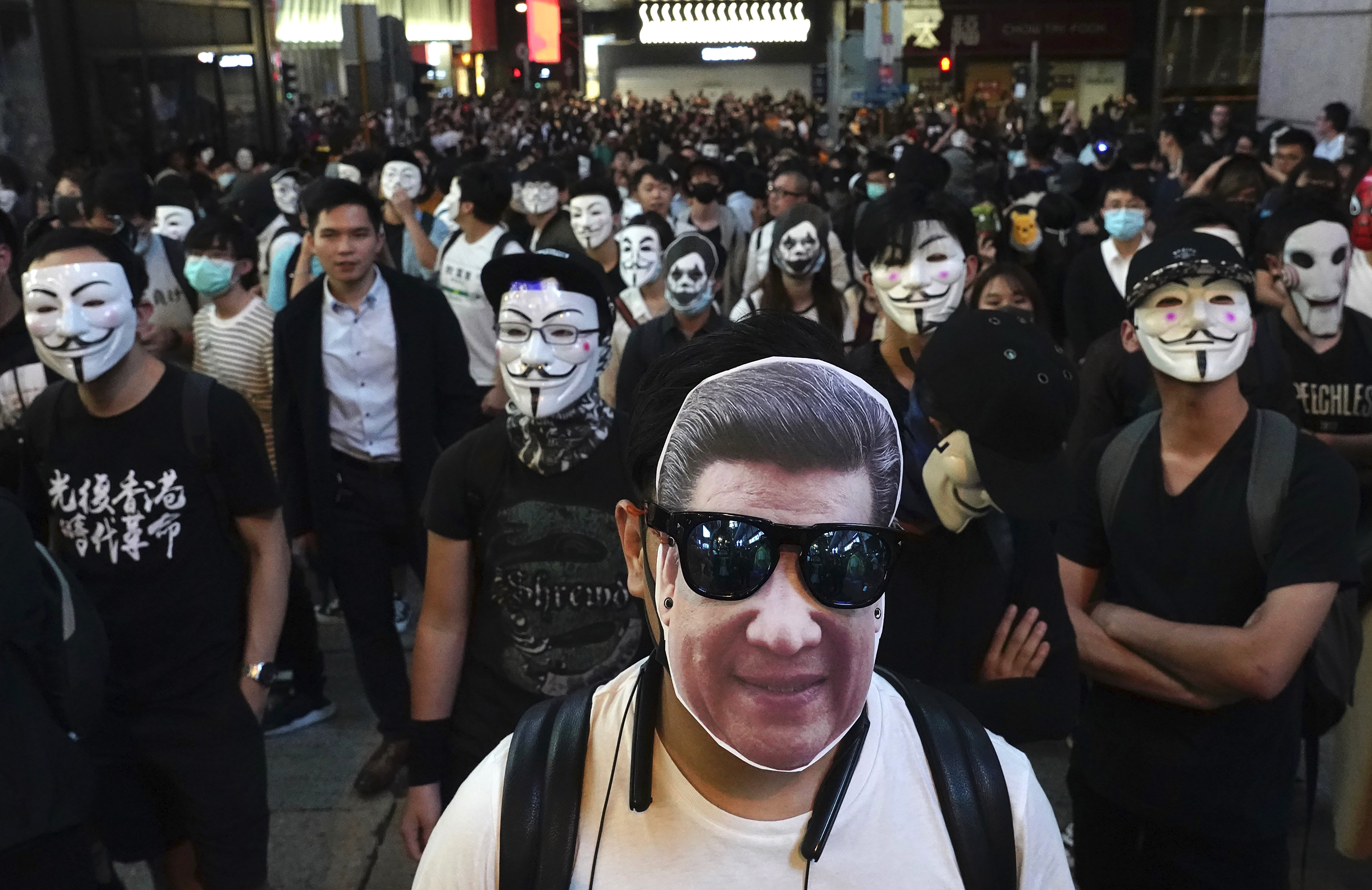 A man wearing a mask of Chinese President Xi Jinping stands with peole wearing Guy Fawkes masks on a street in Hong Kong, Thursday, Oct. 31, 2019. Hong Kong authorities are bracing as pro-democracy protesters urged people on Thursday to celebrate Halloween by wearing masks on a march in defiance of a government ban on face coverings. (AP Photo/Vincent Yu)