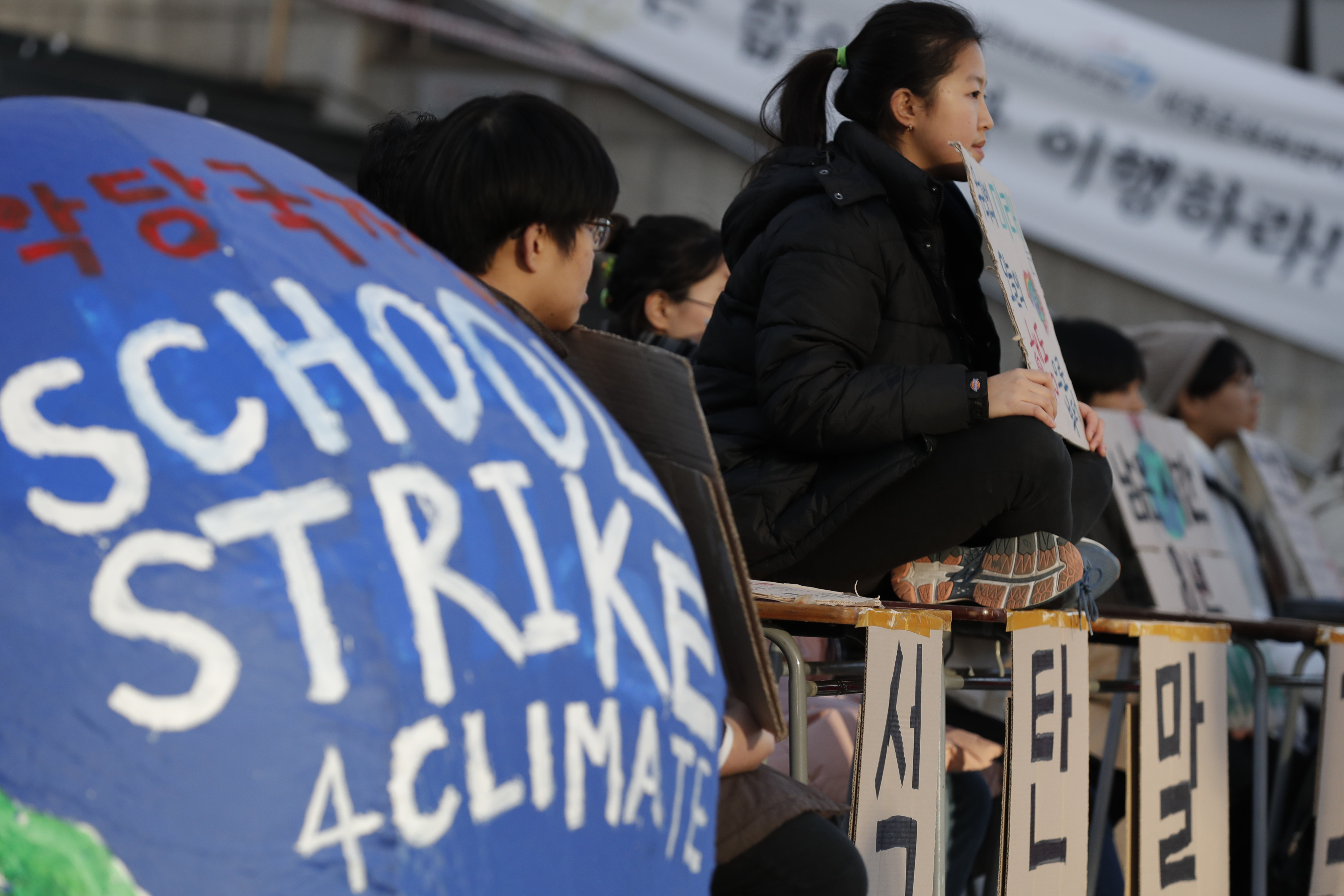 South Korean students hold banners during a rally for climate strike for future in Seoul, South Korea, Friday, Nov. 29, 2019. More than 10 students attended the rally demanding their government to take sufficient action against climate change. (AP Photo/Lee Jin-man)