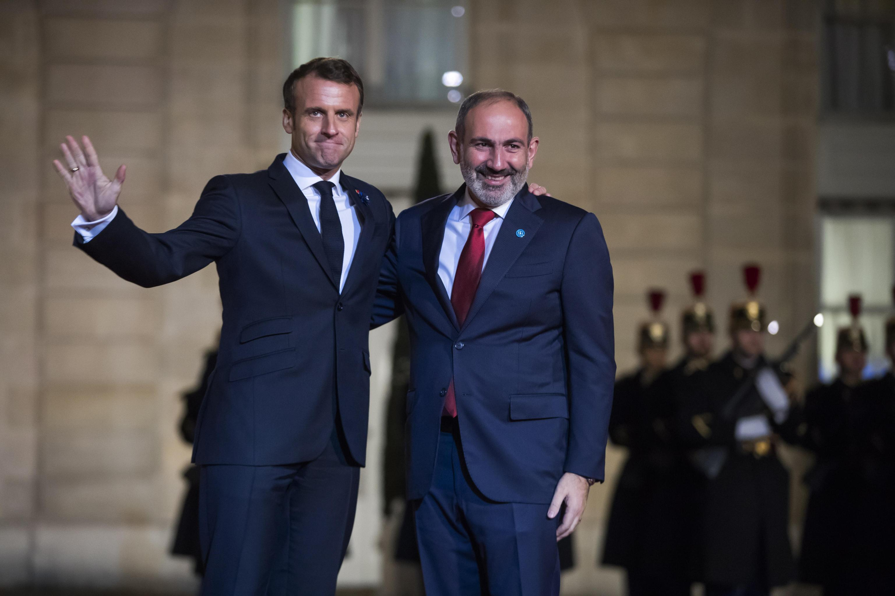 epa07989398 French President Emmanuel Macron (L) welcomes Armenian Prime Minister Nikol Pashinyan (R)  for a dinner held with participants of the Paris Peace Forum, at the Elysee Palace, in Paris, France, 11 November 2019.  EPA/CHRISTOPHE PETIT TESSON
