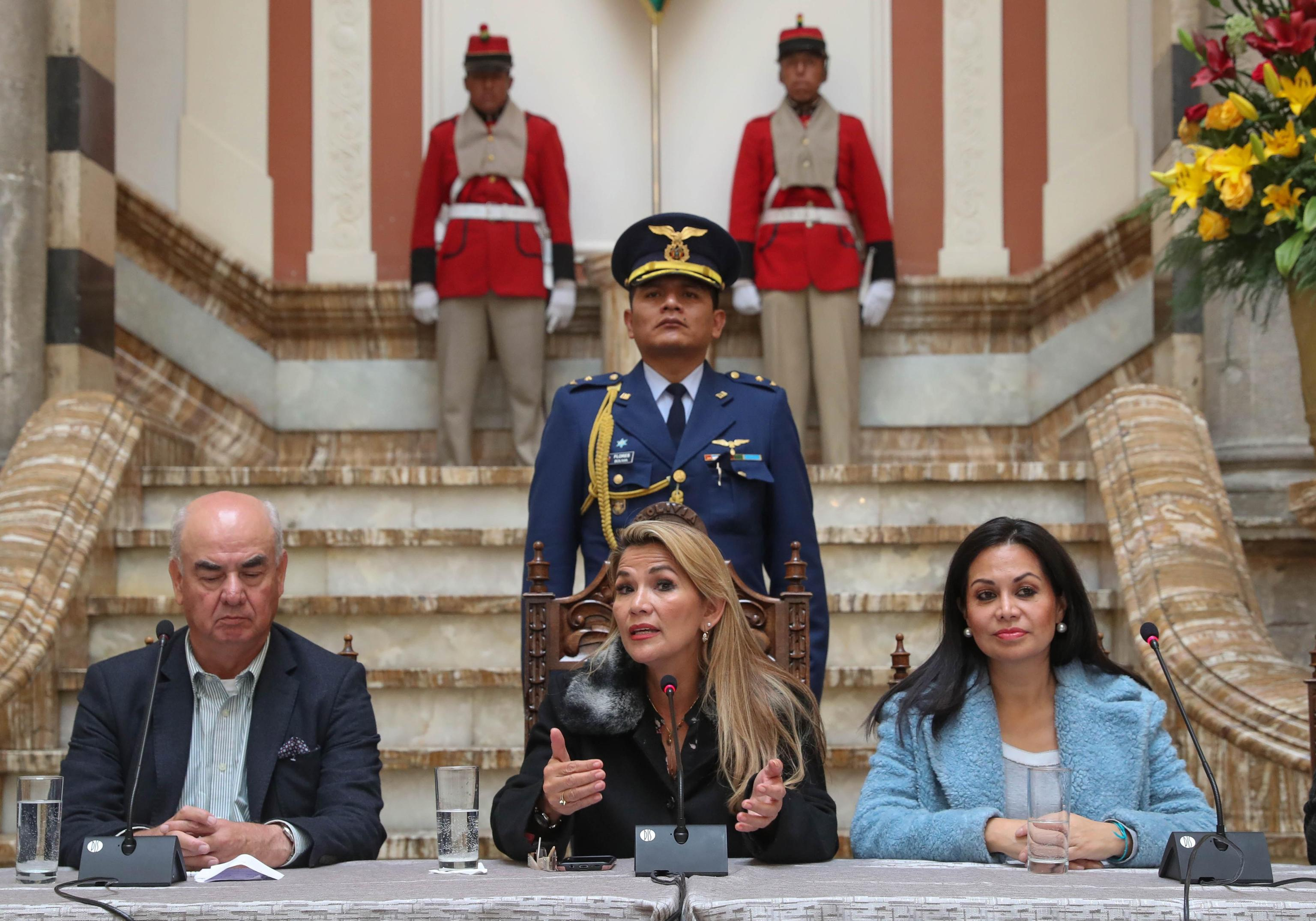 epa07999521 Interim President of Bolivia, Jeanine Anez (C) speaks along with Ministers of Economy, Jose Luis Parada (L) and Minister of Communication, Roxana Lizarraga (R) at a press conference at Government Palace in La Paz, Bolivia, 15 November 2019. Anez announced that this day she hopes to start the process for new elections after the failed elections that led to the resignation of Evo Morales.  EPA/RODRIGO SURA