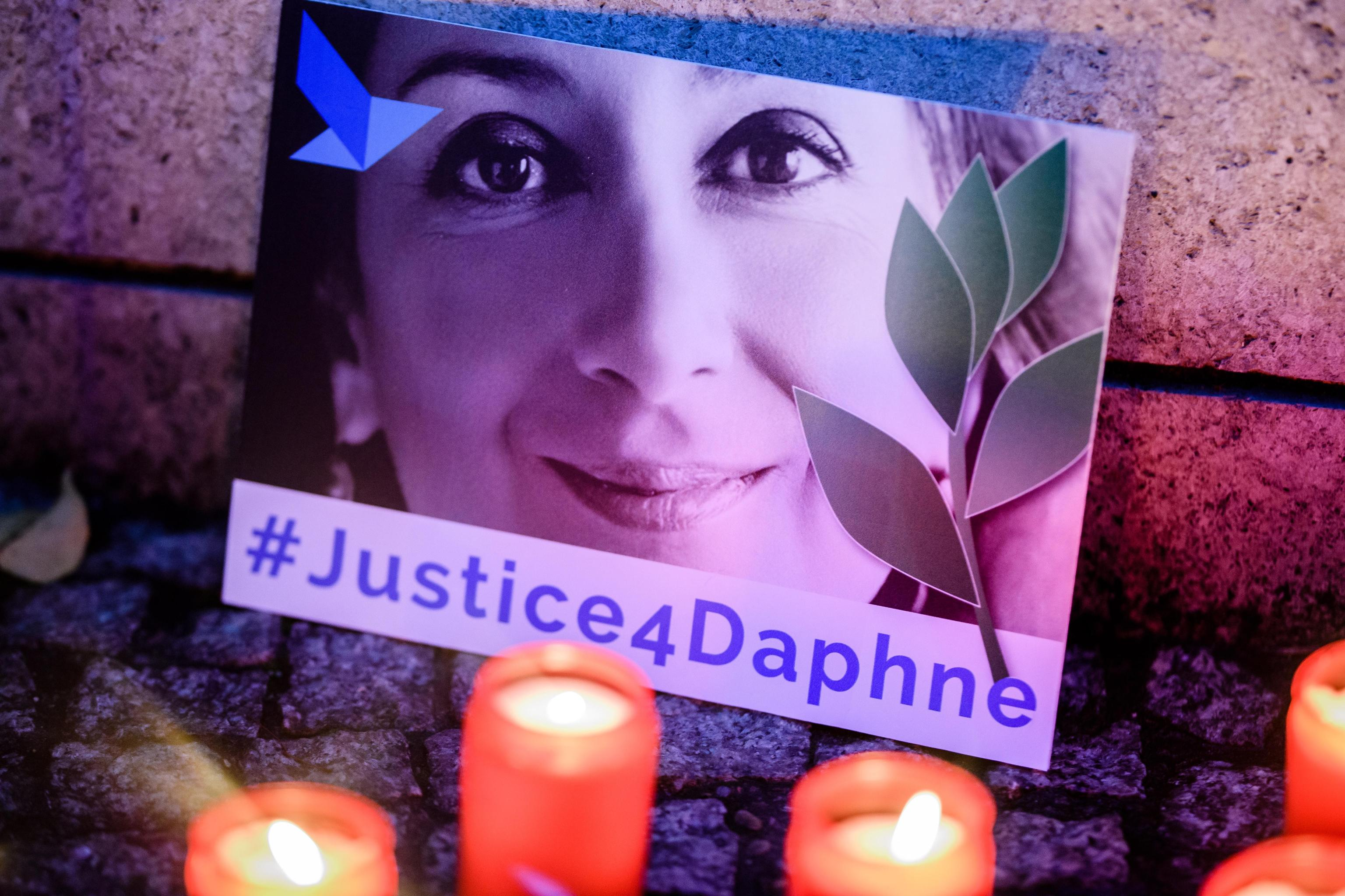 epa07925848 'Justice four Daphne' is written on a cardboard showing a photo of Daphne Caruana Galizia, during a picket in front of the Maltese embassy for murdered journalist Daphne Caruana Galizia in Berlin, Germany, 16 October 2019. Reporters Without Borders organized a picket for murdered journalist Daphne Caruana Galizia, who was killed on 16 October 2017 in Malta, while investigating the Panama Papers case.  EPA/CLEMENS BILAN