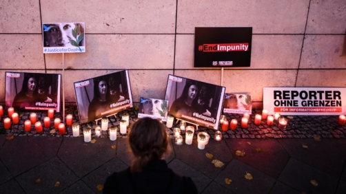 epa07925850 A woman kneels in front of candles and pictures during a picket in front of the Maltese embassy for murdered journalist Daphne Caruana Galizia in Berlin, Germany, 16 October 2019. Reporters Without Borders organized a picket for murdered journalist Daphne Caruana Galizia, who was killed on 16 October 2017 in Malta, while investigating the Panama Papers case.  EPA/CLEMENS BILAN