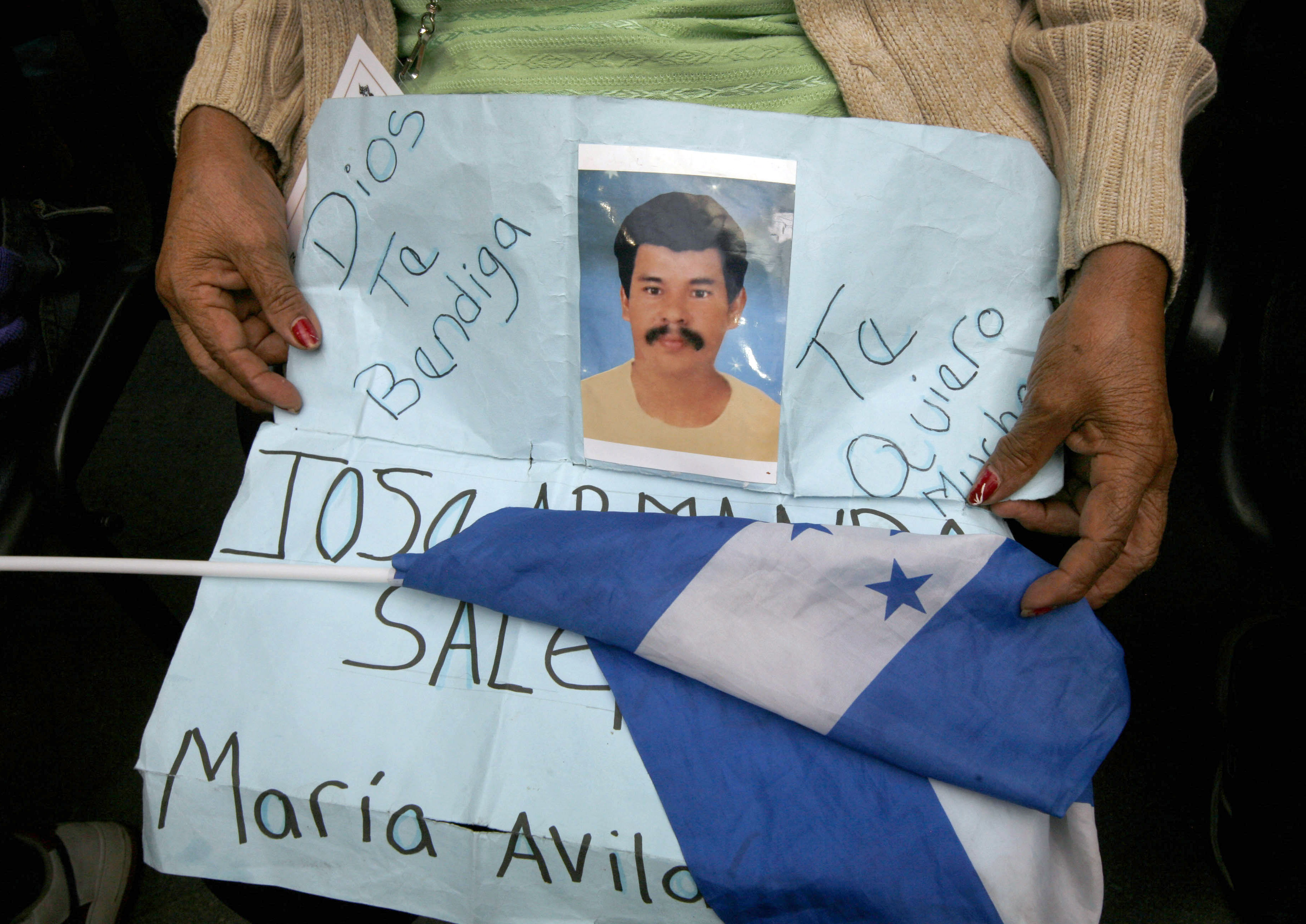 Migrant Maria Avila holds a sign with an image of his missing son, Jose Salgado Avila and a Honduran flag in Mexico City, Monday, Aug. 1, 2011. Hundreds of Central American relatives of dead or missing migrants traveled to Mexico CIty in an effort to pressure Mexican authorities to do more to guarantee the human rights of migrants traveling north towards the United States. (AP Photo/ Marco Ugarte)