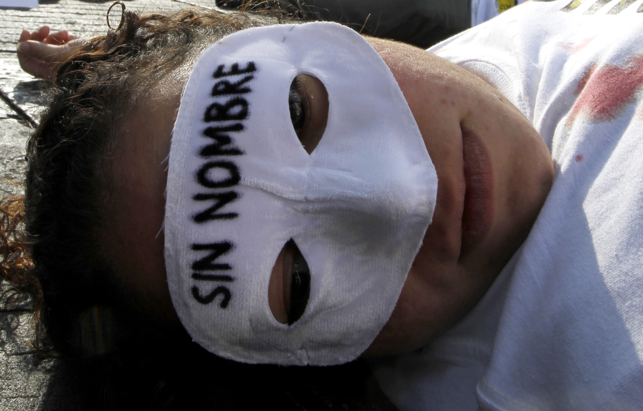 A demonstrator, lying on the floor, wears a mask that reads in Spanish