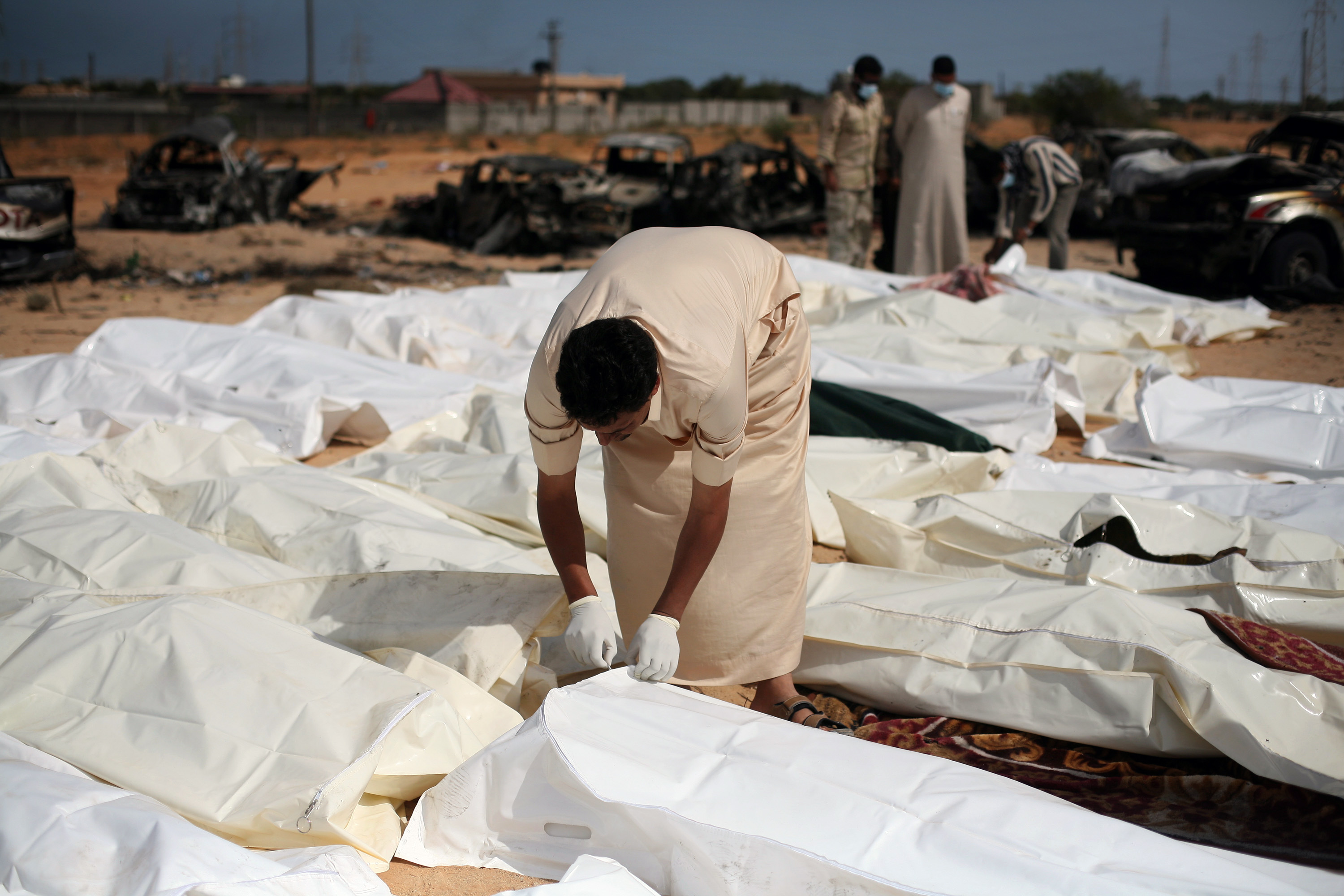 FILE - In this Oct. 22, 2011 file photo, a revolutionary fighter zips a body bag containing one of nearly 30 bodies of Gadhafi loyalists killed in Sirte, Libya, during the city's fall. Libyan rebels appear to have
