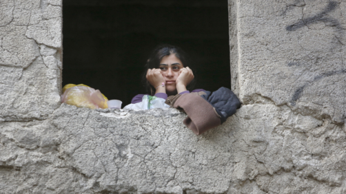 In this Saturday, May 12, 2018 picture, a migrant woman looks out the window of the abandoned building of a former hotel, now serving as a shelter in the western Bosnian town of Bihac, Bosnia. A senior European human rights official has urged Bosnia to improve its assistance to migrants, as the war-scarred country struggles to cope with a growing influx of people trying to reach Western Europe.(AP Photo/Amel Emric)