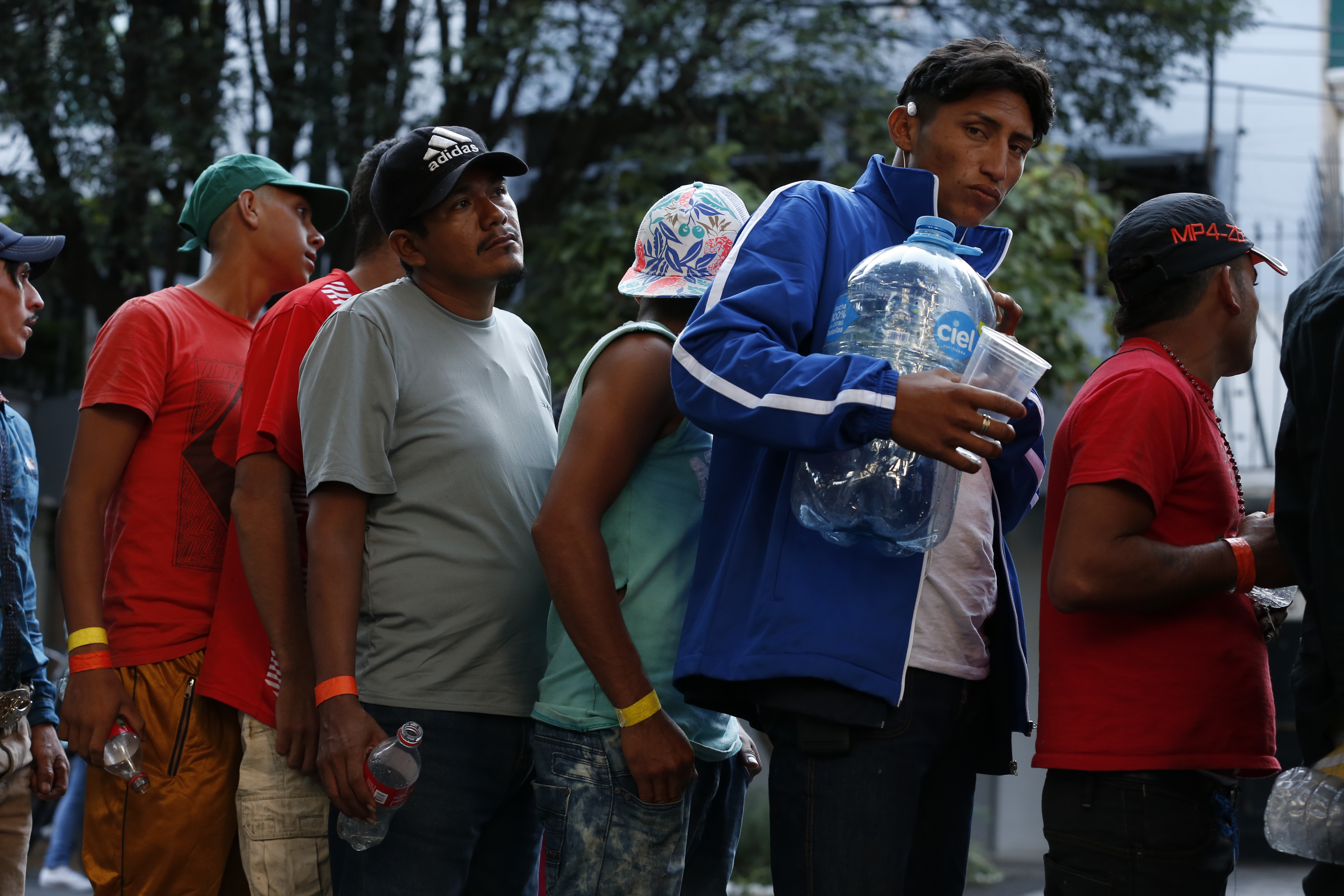 Men line up for donated drinking water, after scores of Central American migrants, representing the thousands participating in a caravan trying to reach the U.S. border, undertook an hours-long march to the office of the United Nations' humans rights body in Mexico City, Thursday, Nov. 8, 2018. Members of the caravan which has stopped in Mexico City demanded buses to take them to the U.S. border, saying it is too cold and dangerous to continue walking and hitchhiking.(AP Photo/Rebecca Blackwell)