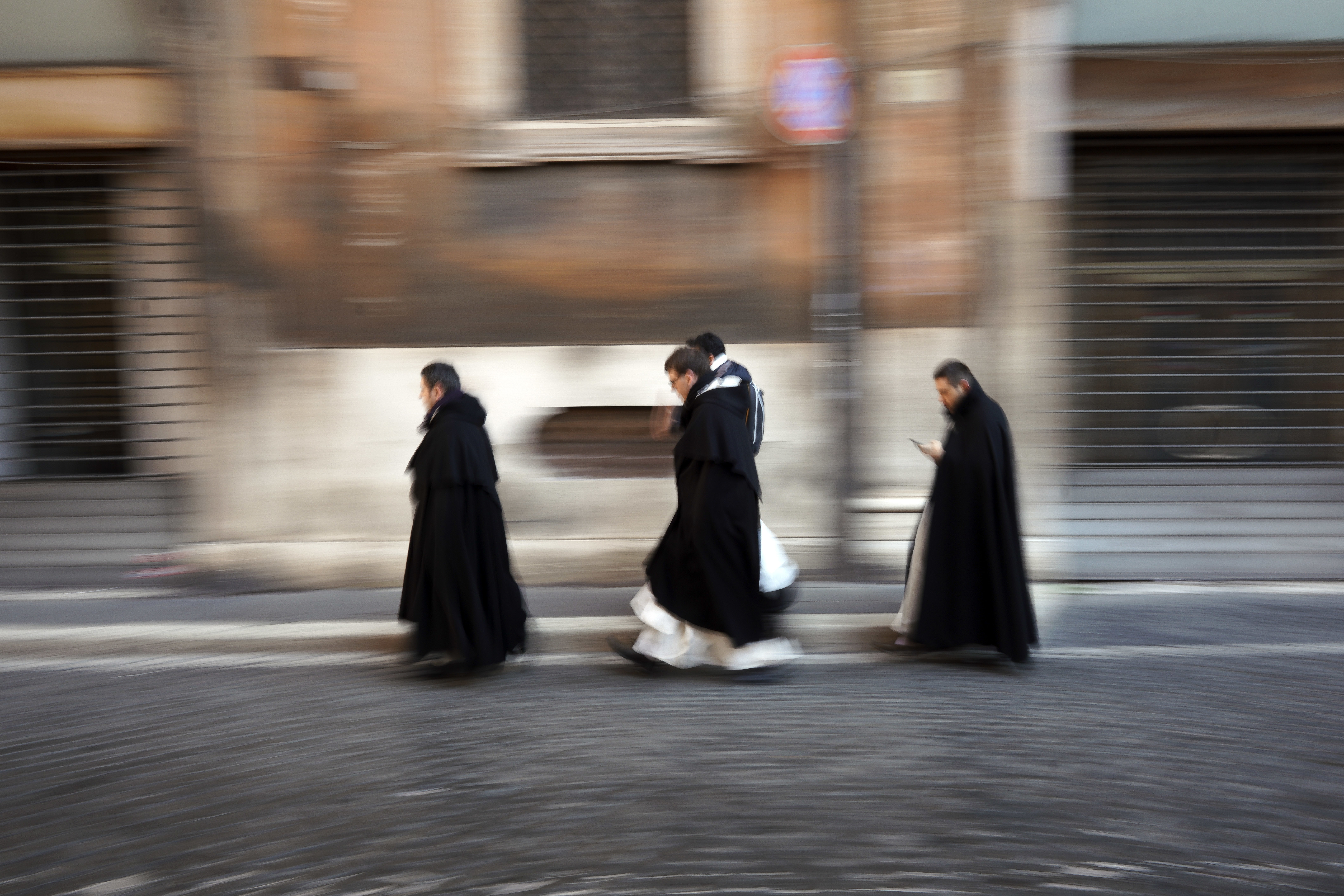 Priests walk in a street in downtown Rome, Monday, Jan. 7, 2019. (AP Photo/Andrew Medichini)