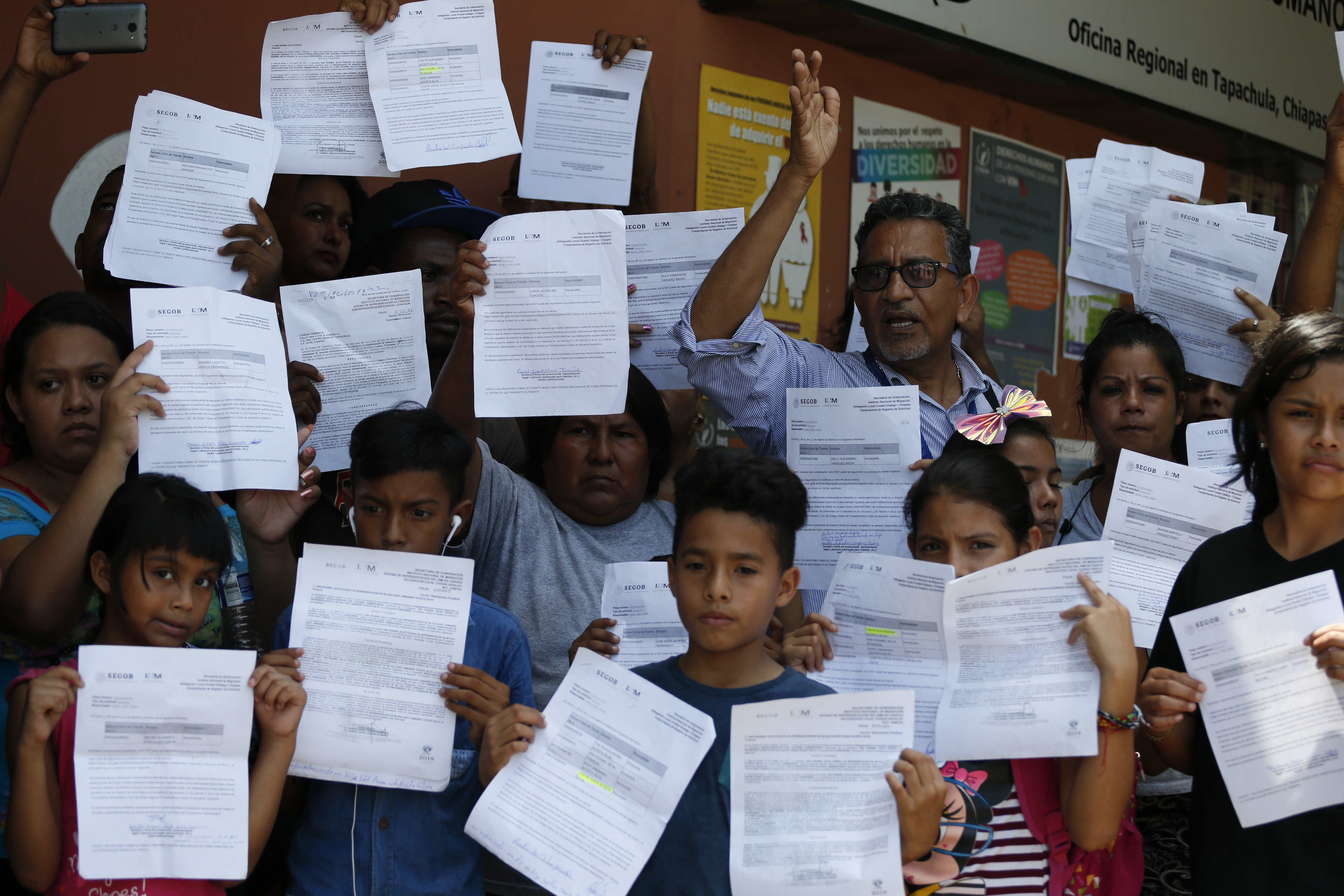 Human rights activist Luis Villagran speaks as migrants hold up their Mexican migration paperwork during a small protest against long wait times for receiving documents to legally stay in Mexico, outside the office of the national Human Rights Commission in Tapachula, Mexico, Wednesday, June 19, 2019. Villagran led a group of several dozens migrants to the offices to protest in front of the press, before entering with a representative group of migrants from several countries to present the group's complaints.(AP Photo/Rebecca Blackwell)