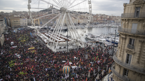 Protesters march during a mass stirke in the Old Port of Marseille, southern France, Wednesday, Dec. 5, 2019. Workers across the public sector fear President Emmanuel Macron's reform will force them to work longer and shrink their pensions. AP Photo/Daniel Cole)