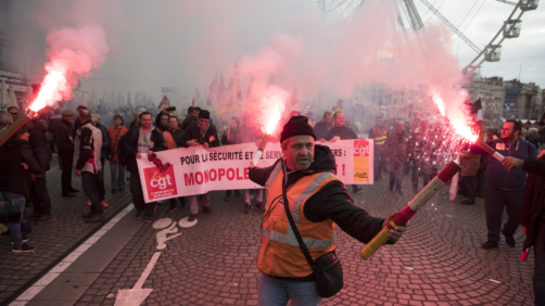 A railworker holds a flare during a mass stirke in the Old Port of Marseille, southern France, Wednesday, Dec. 5, 2019. Workers across the public sector fear President Emmanuel Macron's reform will force them to work longer and shrink their pensions. AP Photo/Daniel Cole)