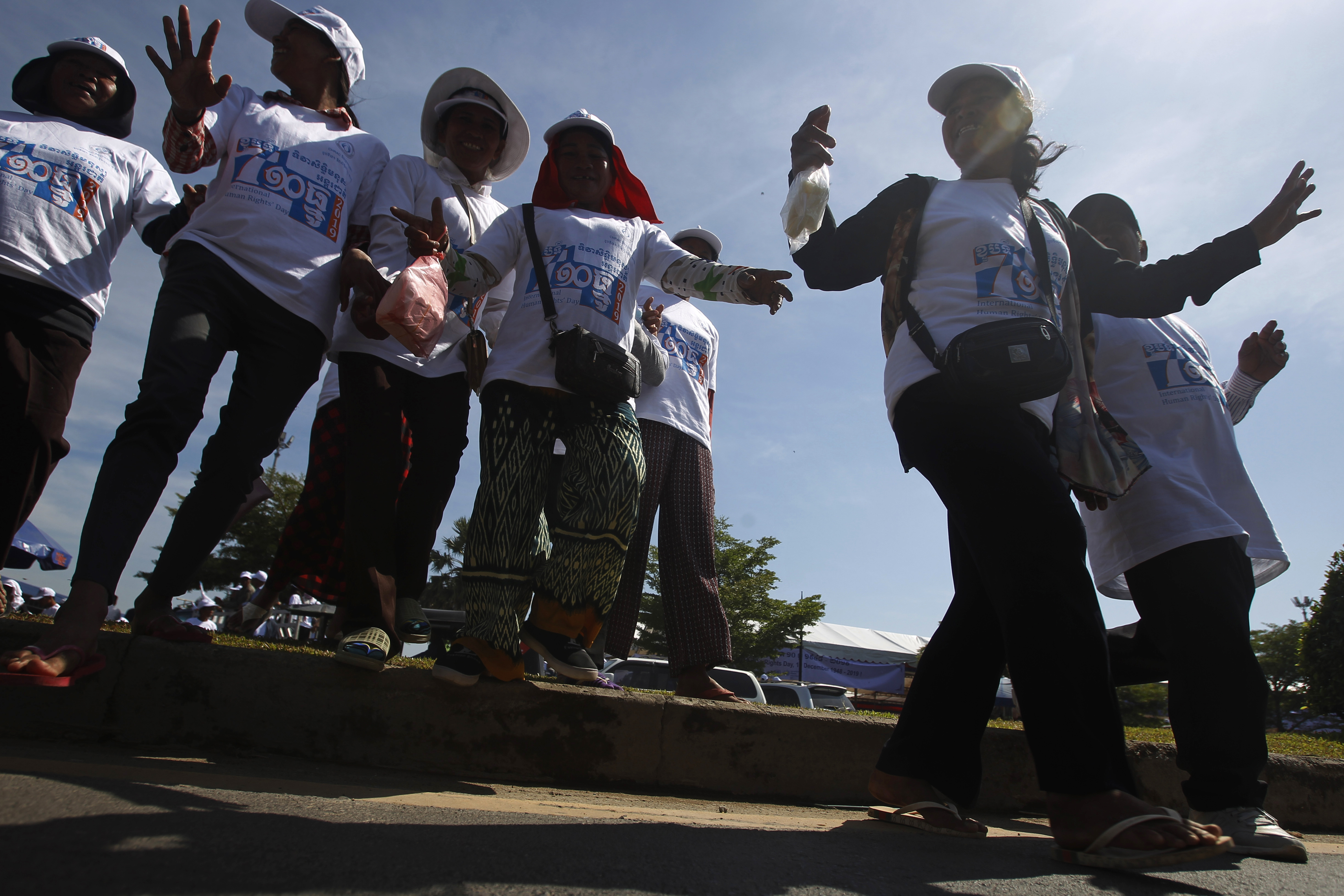 Cambodian factory workers walk across the main road after they participate in a celebration to mark the Human Rights Day at democracy square in Phnom Penh, Cambodia, Tuesday, Dec. 10, 2019. The United Nation's adopted Dec. 10 as the international human rights day in 1948 and has been observed annually ever since. (AP Photo/Heng Sinith)