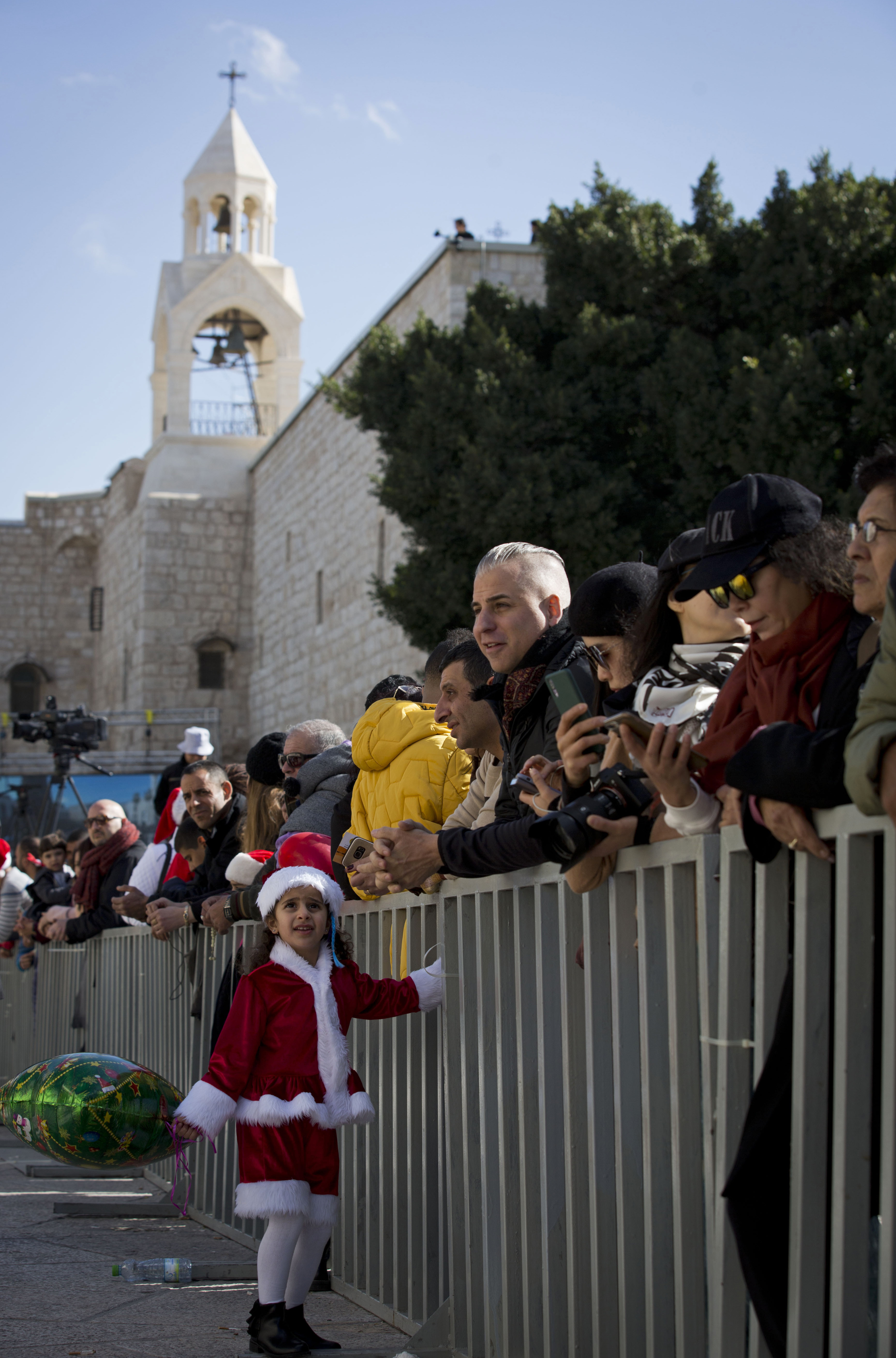 A girl dressed as Santa Claus watches Christmas celebrations outside the Church of the Nativity, built atop the site where Christians believe Jesus Christ was born, on Christmas Eve, in the West Bank City of Bethlehem, Tuesday, Dec. 24, 2019. (AP Photo/Majdi Mohammed)