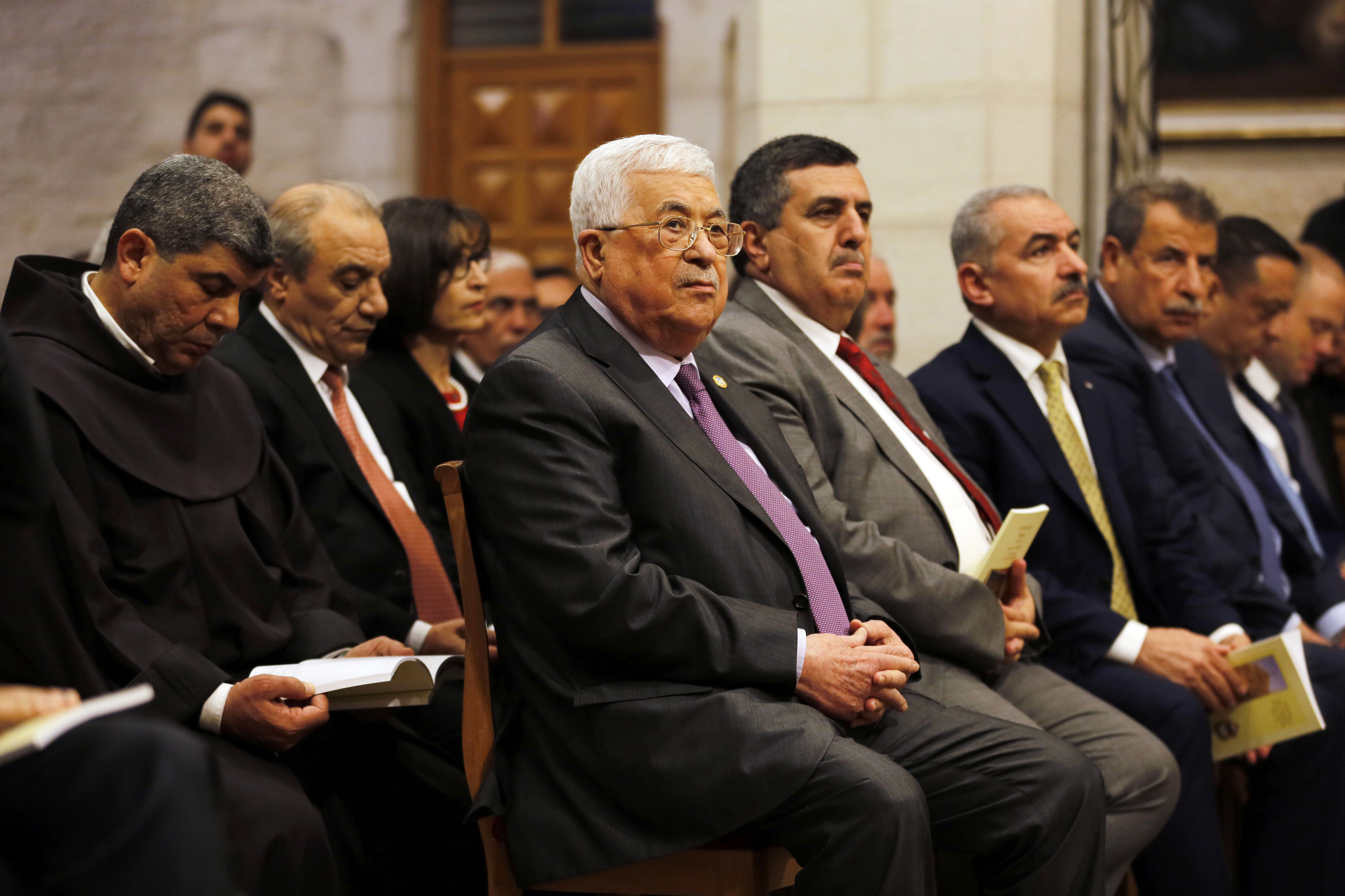 Palestinian President Mahmoud Abbas attends a Christmas midnight mass in the Church of the Nativity in the West Bank town of Bethlehem on Wednesday, Dec. 25, 2019. The Church of the Nativity, where Christians believe Jesus was born, hosted Palestinian dignitaries and pilgrims from around the world for the midnight Mass. (Mussa Qawasma/Pool Photo via AP)