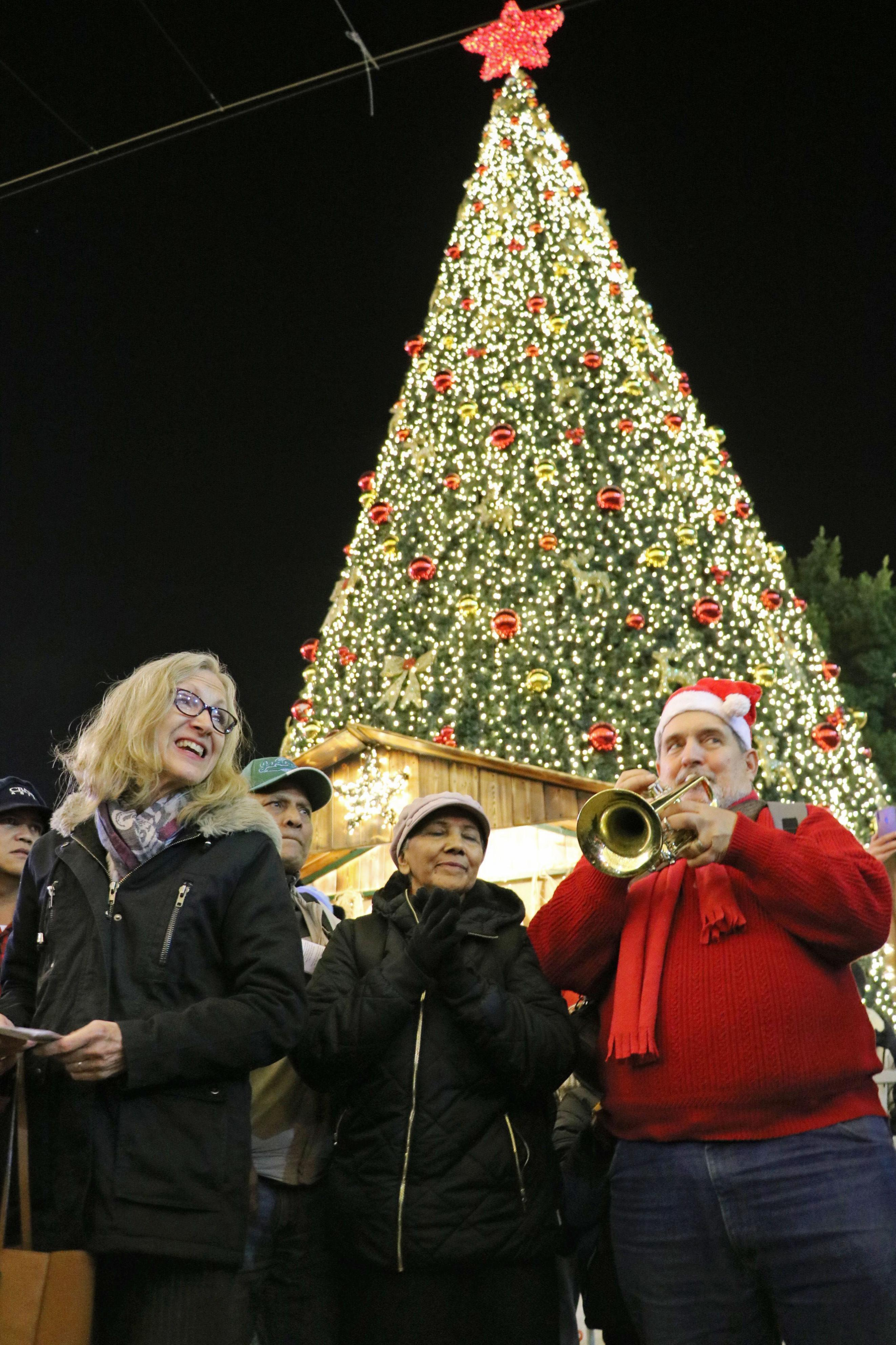 People sing in front of a Christmas tree near the Church of the Nativity in Bethlehem on Dec. 24, 2019. (Kyodo via AP Images) ==Kyodo