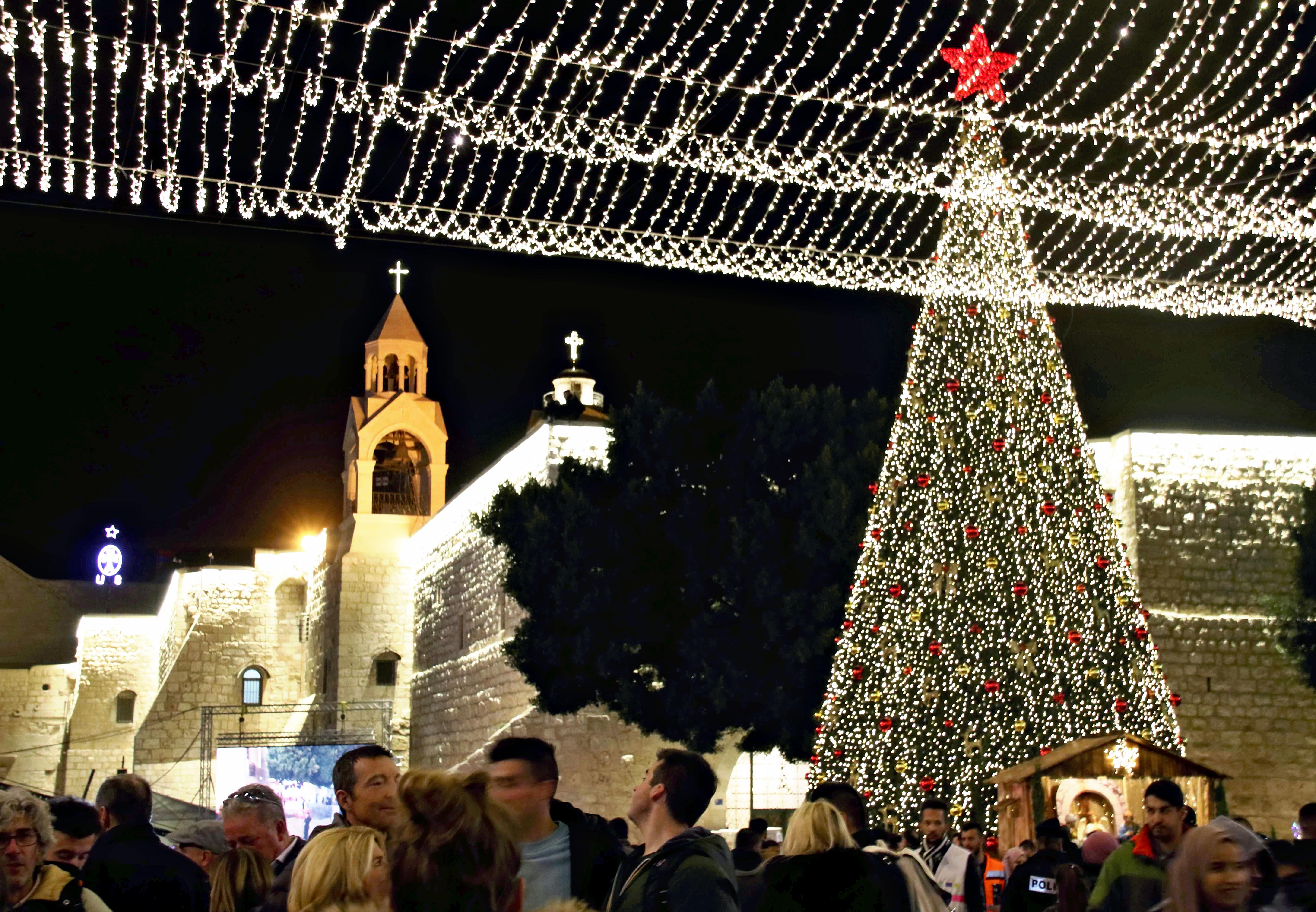 People celebrate Christmas in front of the Church of the Nativity, or Basilica of the Nativity, in Bethlehem on Dec. 24, 2019.( The Yomiuri Shimbun via AP Images )