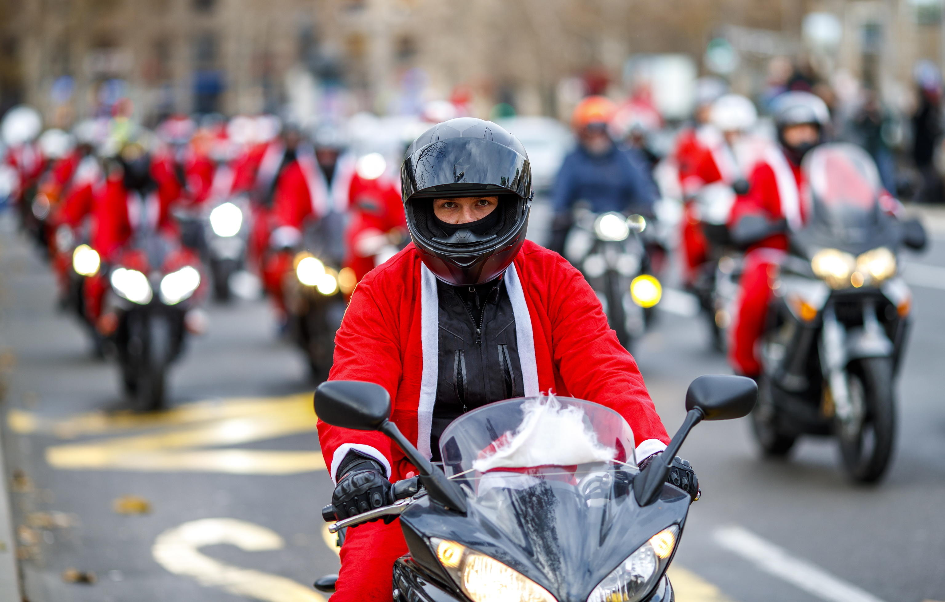 epa08084753 A Serbian motorcyclists dressed in Santa costume drive through the streets of the city center of Belgrade, Serbia, 21 December 2019. A group of Serbian motorcycle enthusiasts gathered in the Serbian capital for a joint ride to the bring Christmas gifts for underprivileged children.  EPA/SRDJAN SUKI
