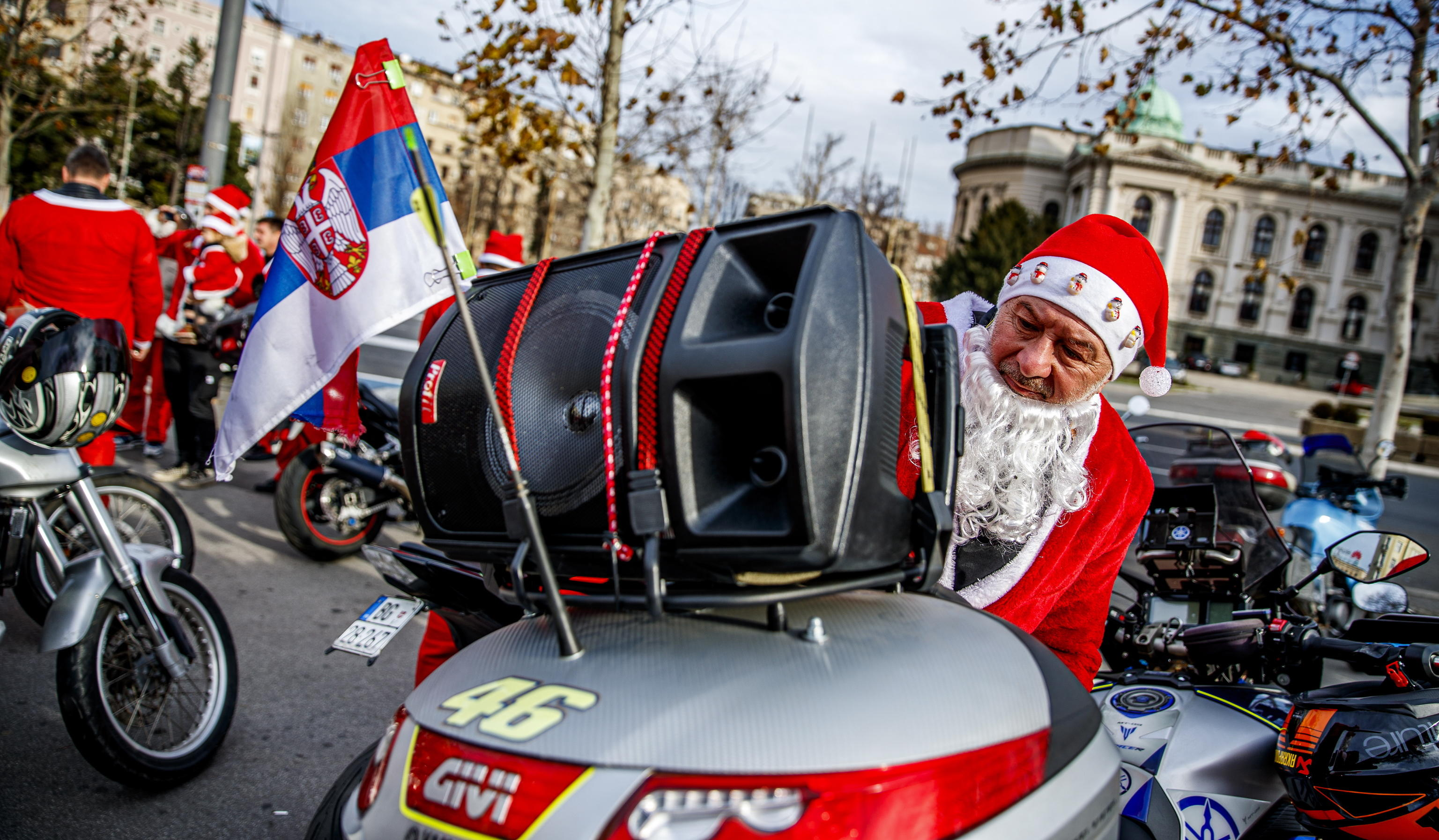 epa08084754 A Serbian motorcyclist dressed in Santa costume gets ready for a drive in Belgrade, Serbia, 21 December 2019. A group of Serbian motorcycle enthusiasts gathered in the Serbian capital for a joint ride to the bring Christmas gifts for underprivileged children.  EPA/SRDJAN SUKI