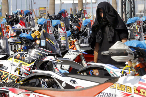 A visitor covers his head as he watches motorbikes parked in Dakar village, in Jiddah, Saudi Arabia, Saturday, Jan. 4, 2020. The Dakar Rally is swapping South America for Saudi Arabia. Created in 1977, the rally was raced across Africa until terror threats in Mauritania led organizers to cancel the 2008 edition. (AP Photo/Amr Nabil)