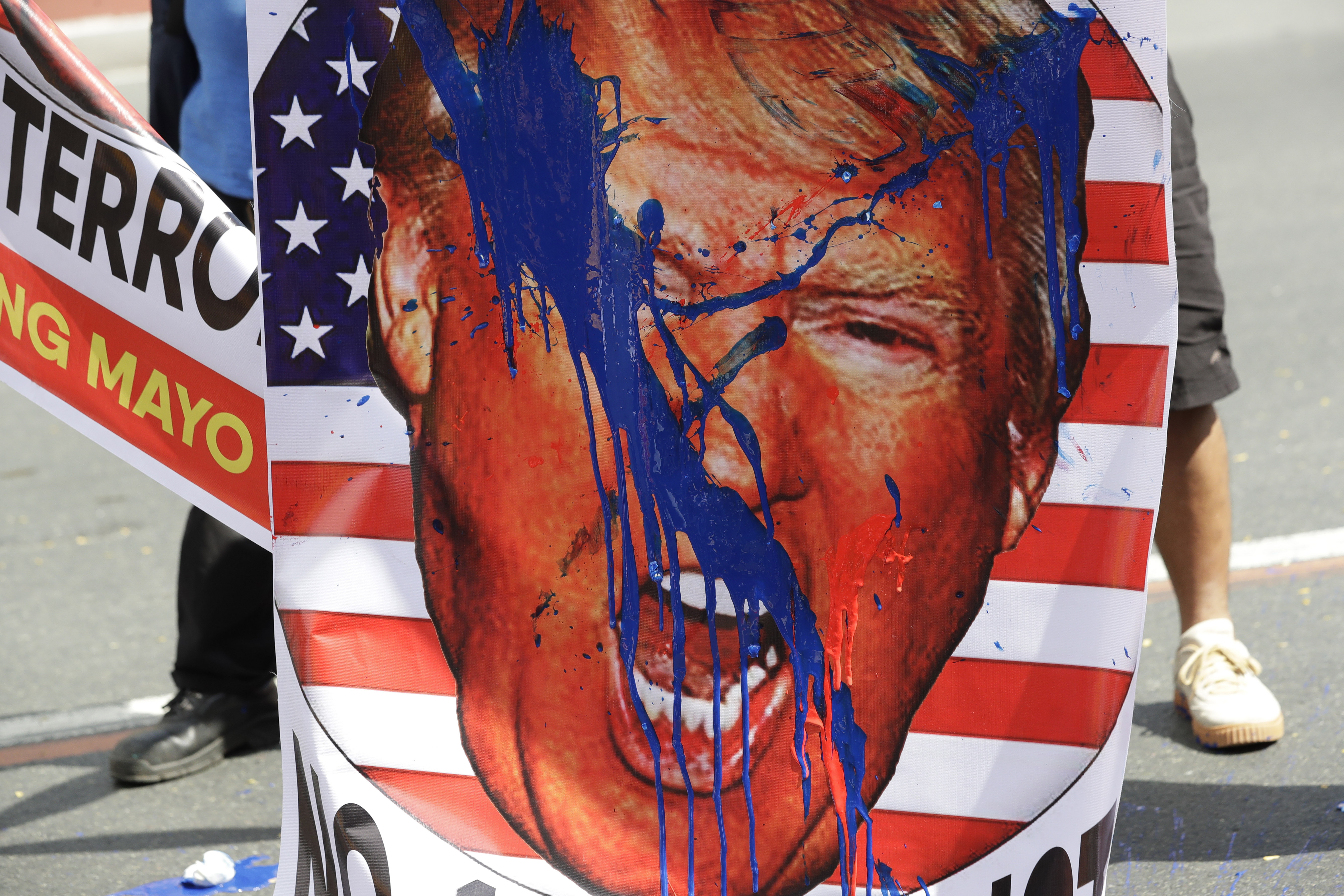 An image of U.S. President Donald Trump is splashed with paint by protesters as they hold a rally opposing the recent attack of the U.S. against Iran, where it killed Gen. Qassem Soleimani, near the U.S. Embassy in Manila, Philippines, Monday, Jan. 6, 2020. Philippine President Rodrigo Duterte ordered the military to prepare to deploy its aircraft and ships